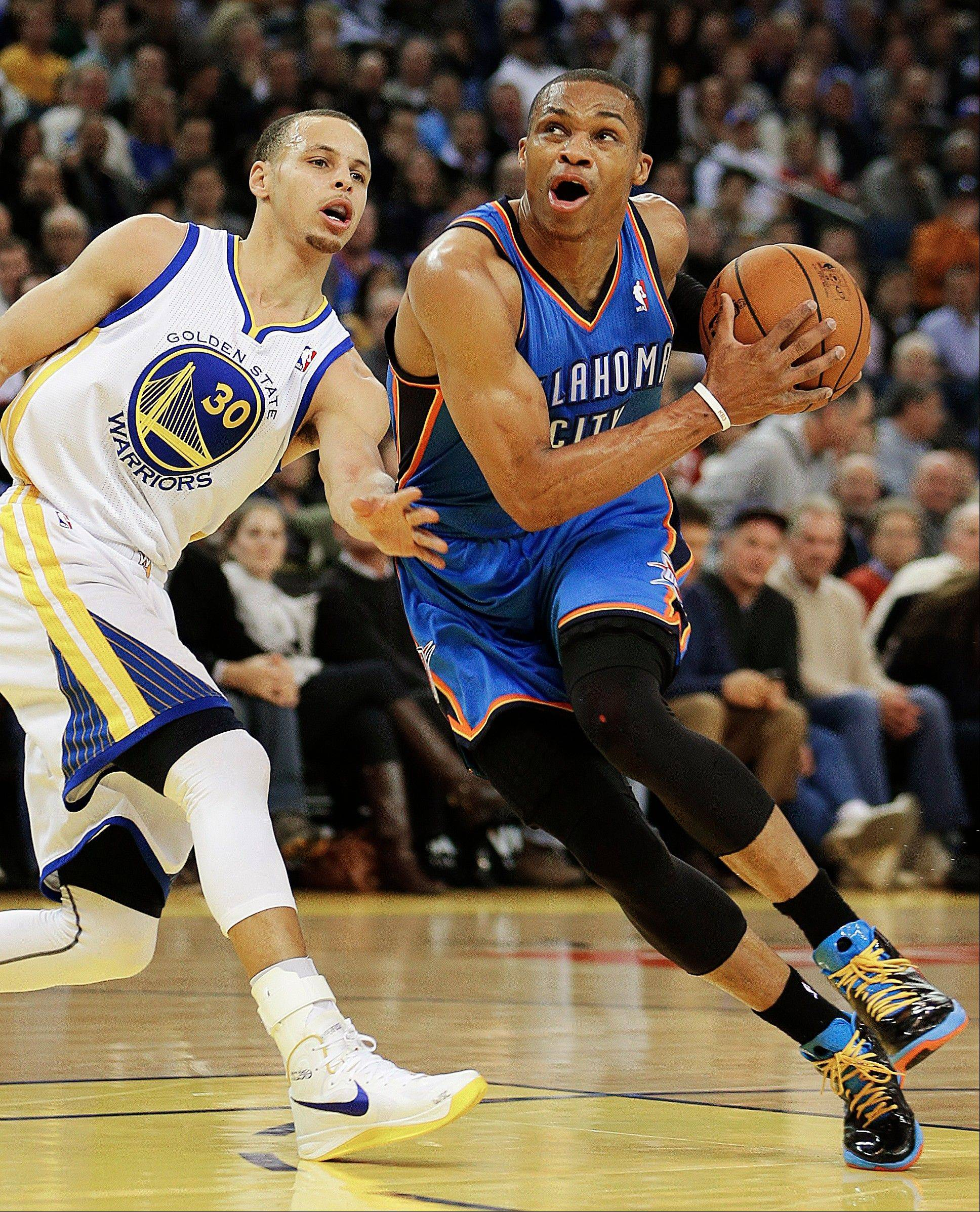 Oklahoma City Thunder's Russell Westbrook, right, drives past Golden State Warriors' Stephen Curry (30) during the first half of an NBA basketball game, Wednesday, Jan. 23, 2013, in Oakland, Calif.