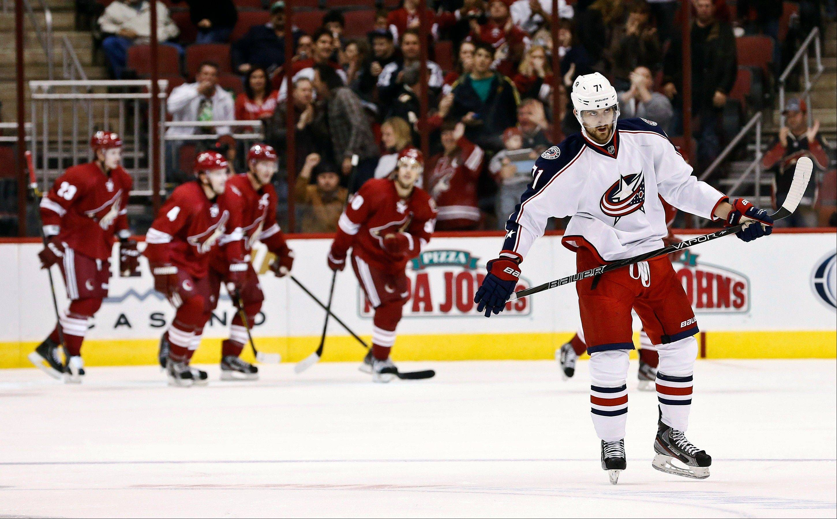 Columbus Blue Jackets' Nick Foligno, right, skates away as the Phoenix Coyotes celebrate a goal by Steve Sullivan during the second period in an NHL hockey game, Wednesday, Jan. 23, 2013, in Glendale, Ariz.