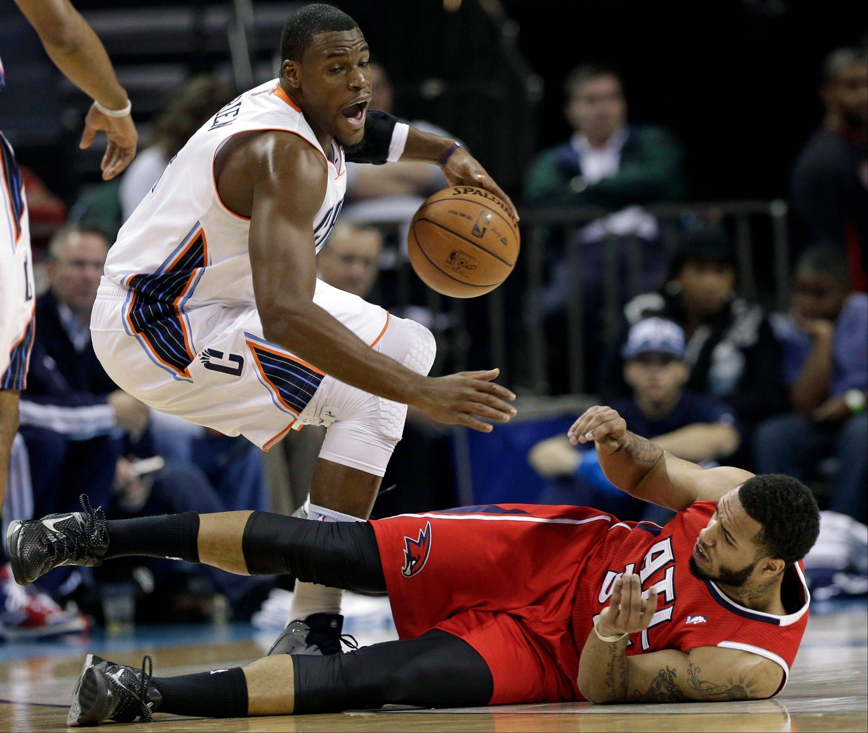 Charlotte Bobcats' Jeff Adrien, top, steals the ball from Atlanta Hawks' Mike Scott, bottom, during the first half of an NBA basketball game Wednesday night in Charlotte, N.C.