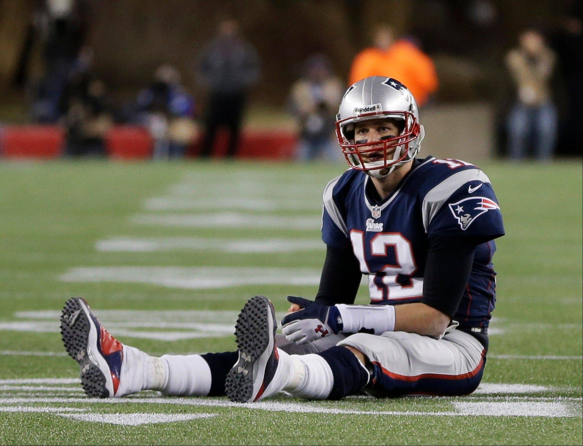 New England Patriots quarterback Tom Brady sits on the field after getting hit during the second half of the NFL football AFC Championship football game against the Baltimore Ravens in Foxborough, Mass., Sunday, Jan. 20, 2013. Brady was fined Wednesday for kicking Ed Reed in the thigh during the game.