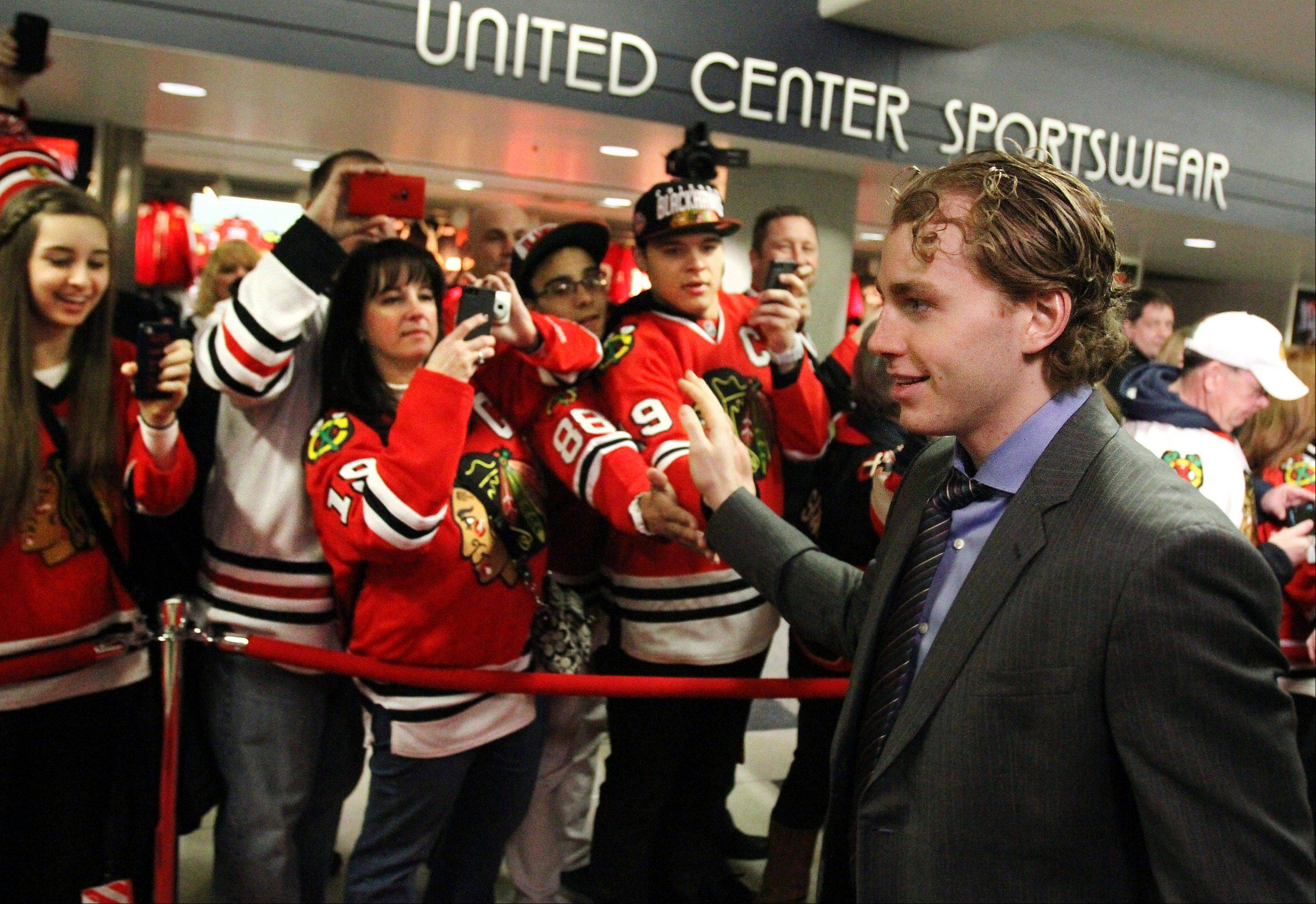 Chicago Blackhawks right wing Patrick Kane high-fives fans as he walks a red carpet introduction before their home opener NHL hockey game against the St. Louis Blues, Tuesday, Jan. 22, 2013, in Chicago.