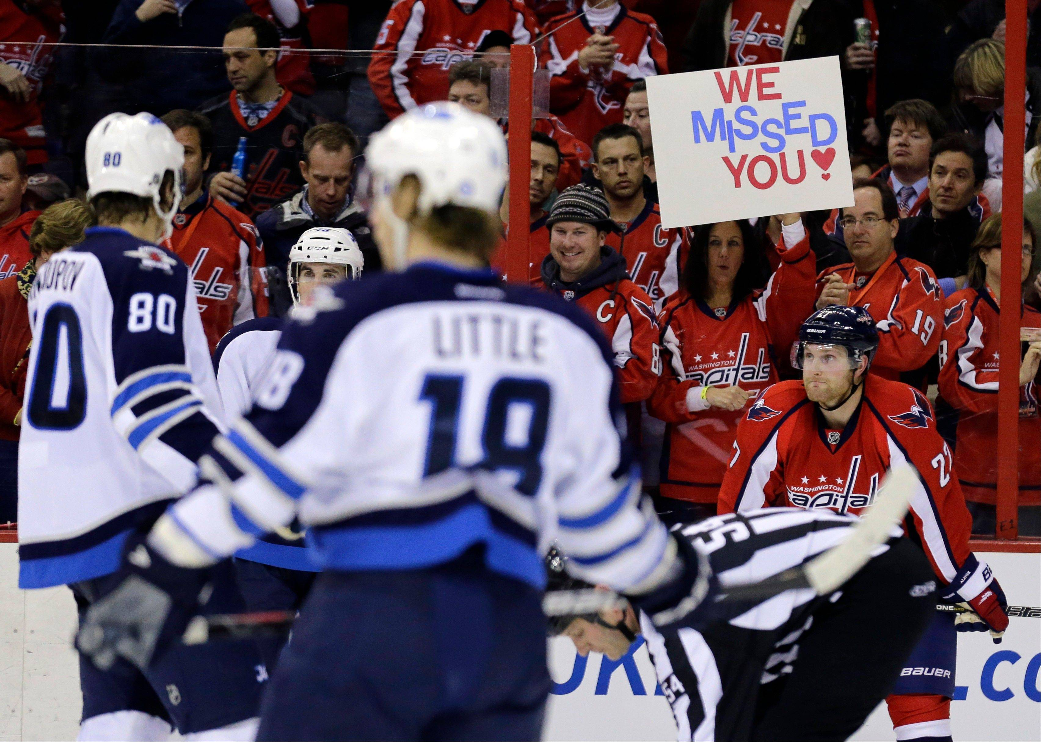 "A fan holds a sign ""We Missed You,"" in the second period of an NHL hockey game with the Washington Capitals against the Winnipeg Jets Tuesday, Jan. 22, 2013 in Washington."