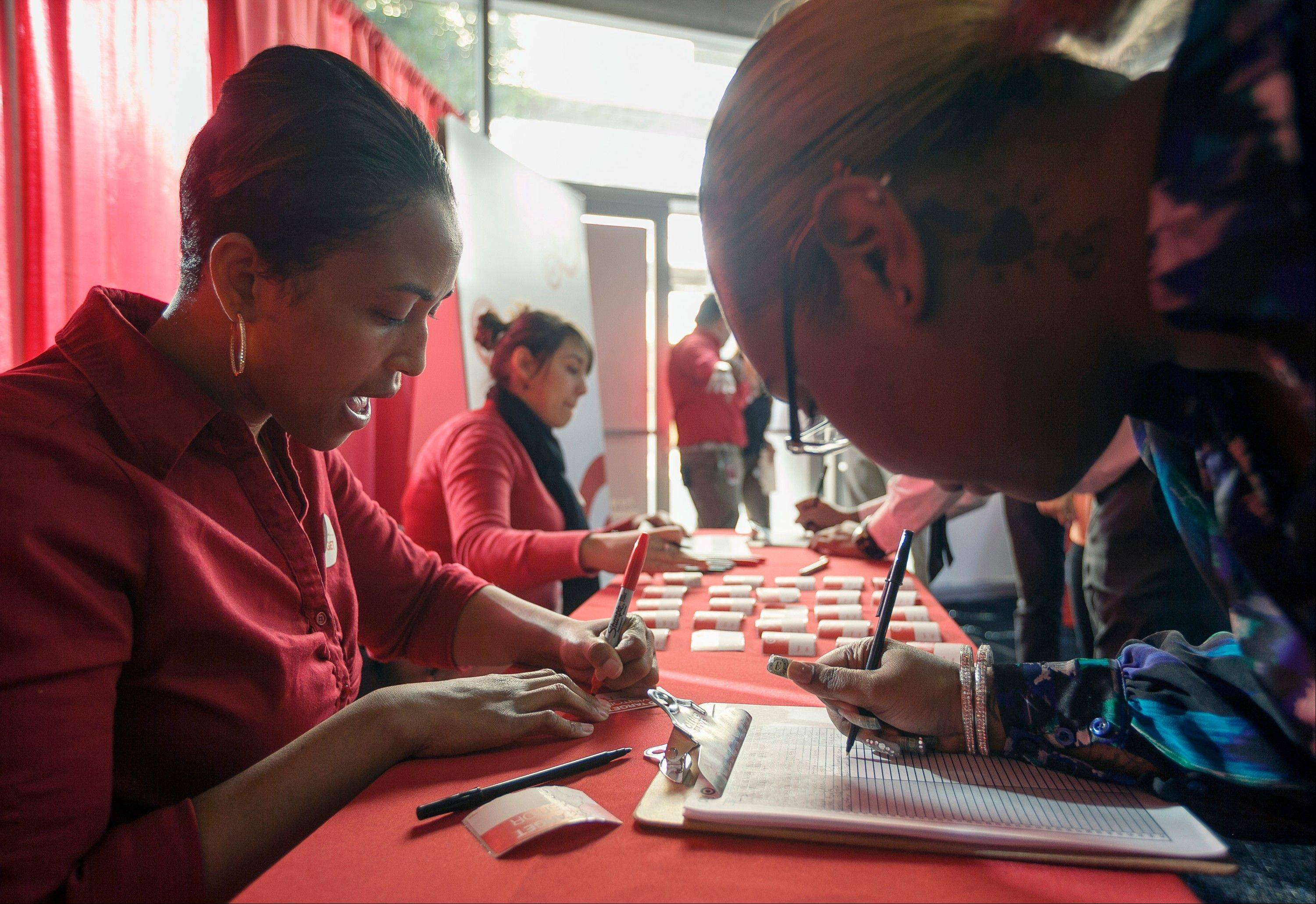 Target human resources team leader Shauna McClain, far left, signs hundreds of arriving job candidates at a Target job fair in Los Angeles.