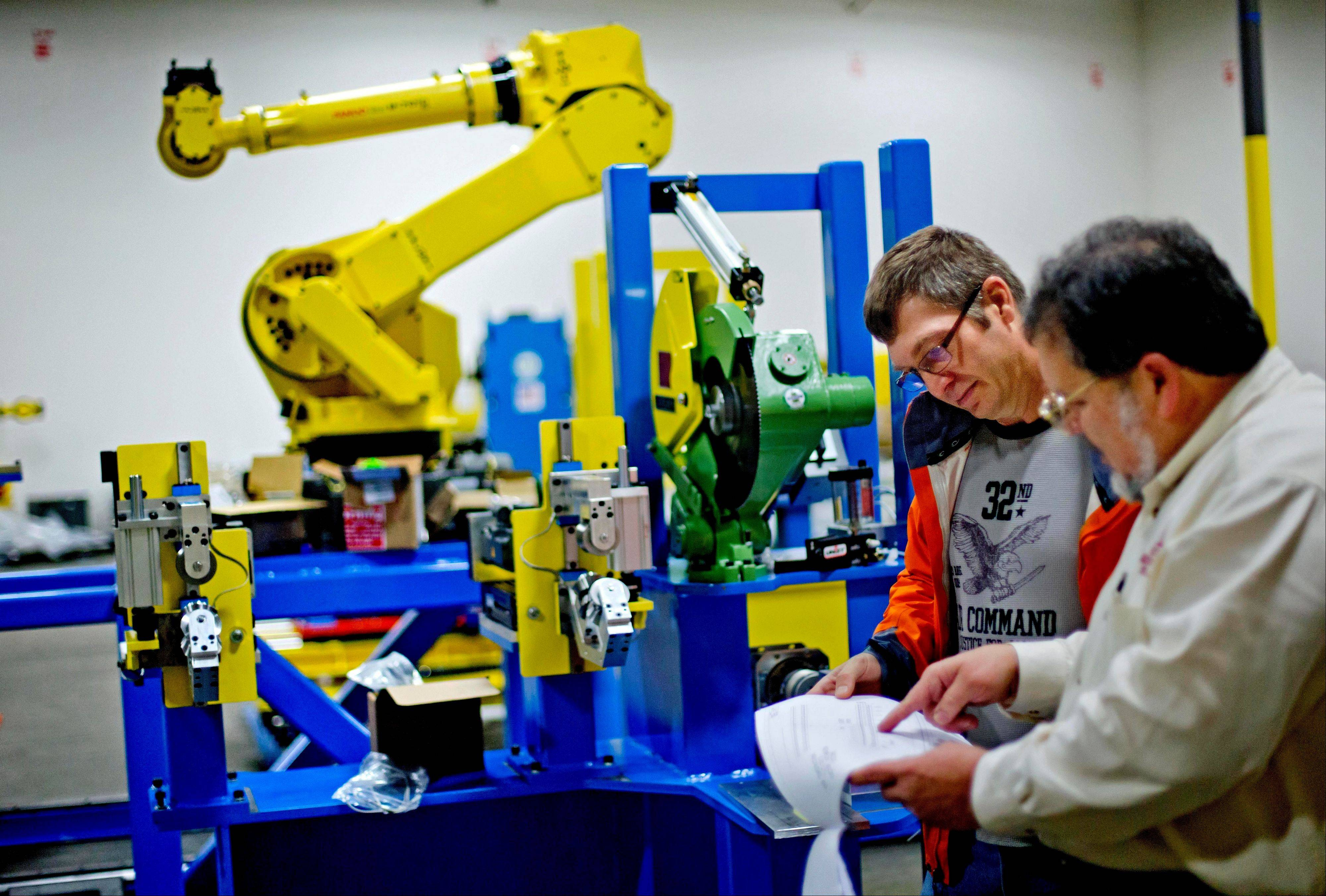 Rosser Pryor, co-owner and President of Factory Automation Systems, right, looks over plans with John Ridgley, project manager, next to a high-performance industrial robot at the company�s Atlanta facility.