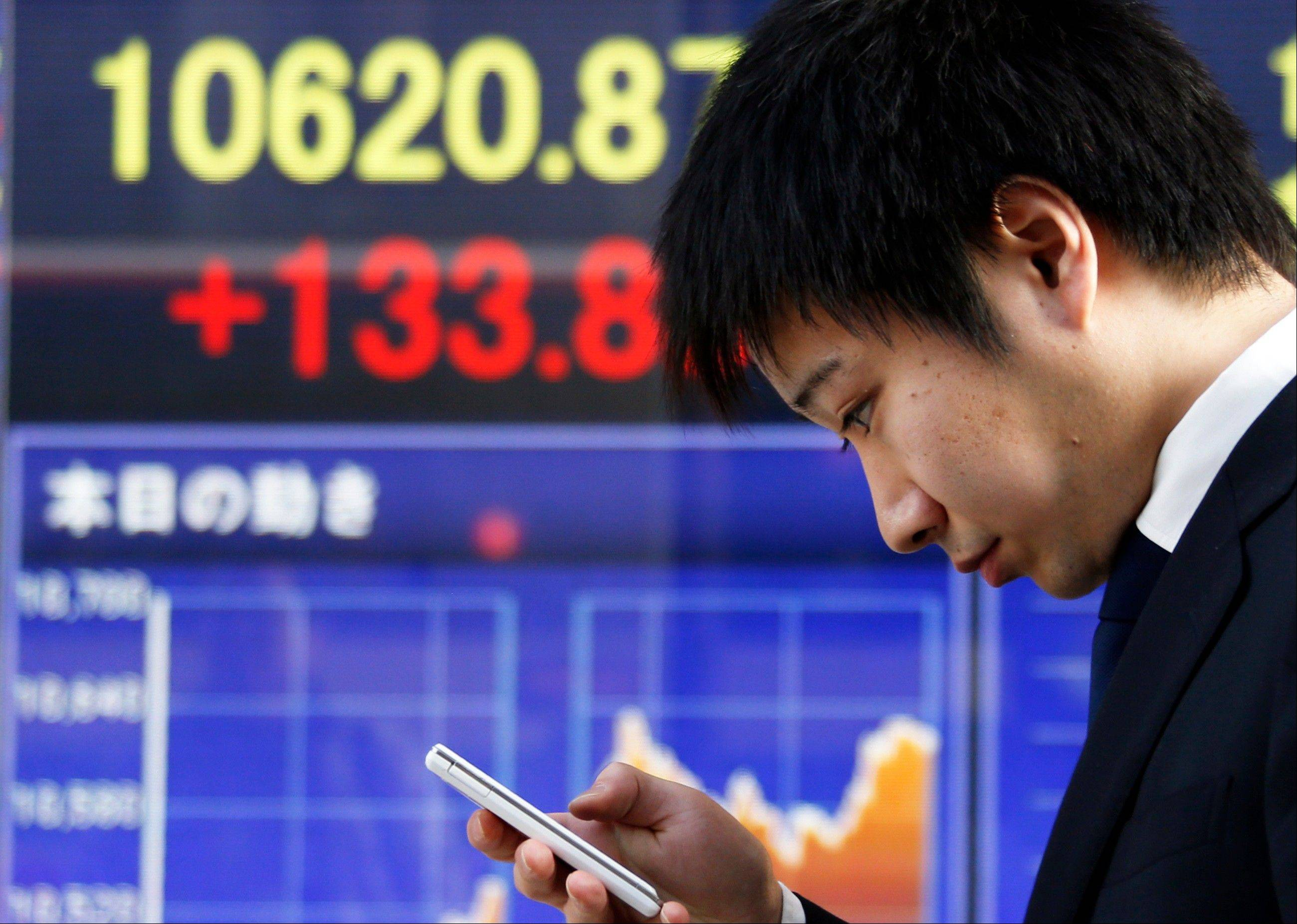 A man looks at his cellphone at an electronic stock board of a securities firm in Tokyo, Thursday.