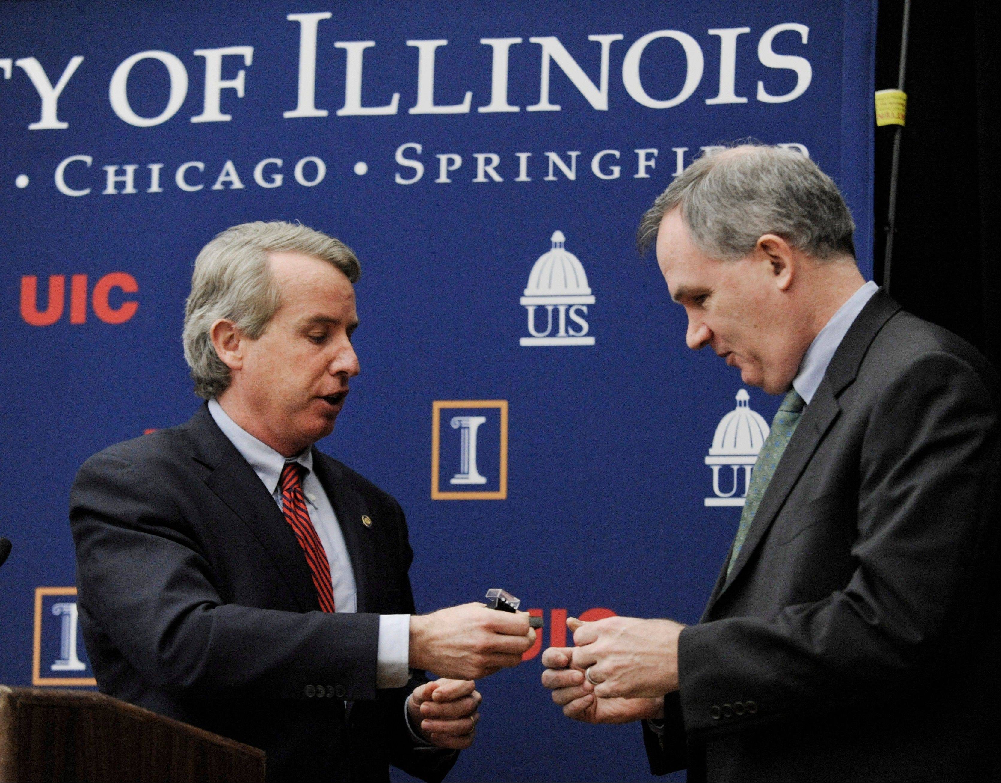 University of Illinois Board of Trustees Chairman Christopher Kennedy, left, congratulates new board member Patrick Fitzgerald during a meeting Thursday at the University of Illinois in Chicago.