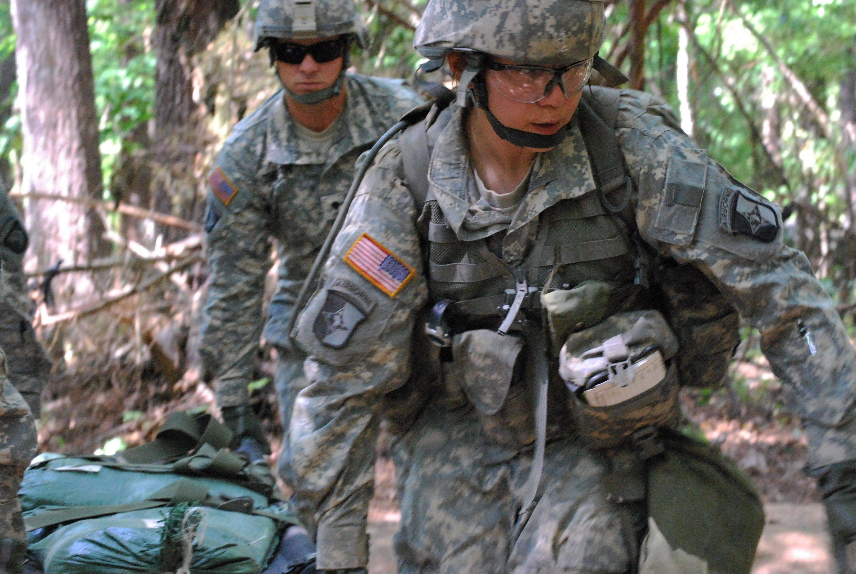 Capt. Sara Rodriguez, 26, of the 101st Airborne Division, carries a litter of sandbags during the Expert Field Medical Badge training at Fort Campbell, Ky. The Pentagon is lifting its ban on women serving in combat, opening hundreds of thousands of front-line positions and potentially elite commando jobs after generations of limits on their service, defense officials said Wednesday.