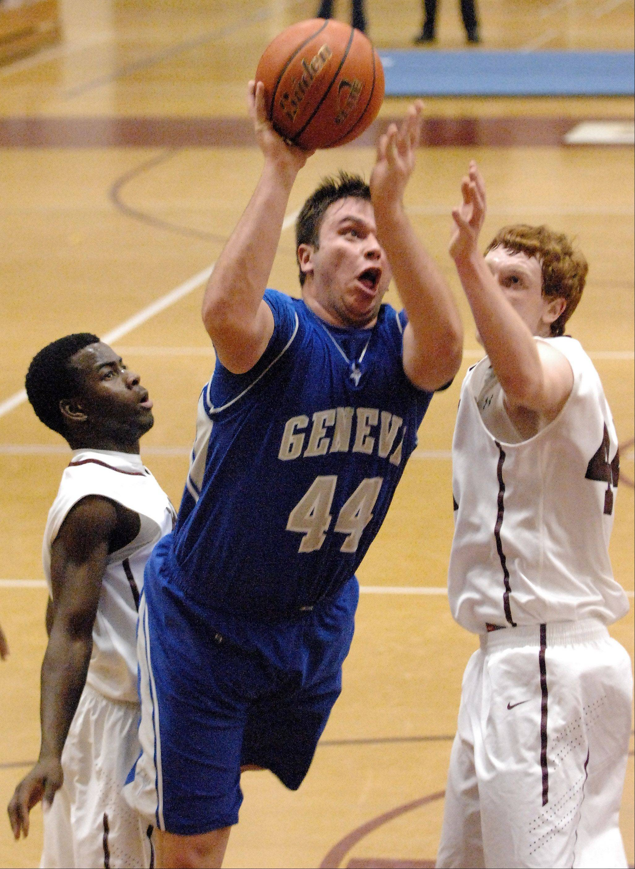 Geneva's Connor Chapman splits a pair of Elgin defenders and puts up a shot during Thursday's game in Elgin.