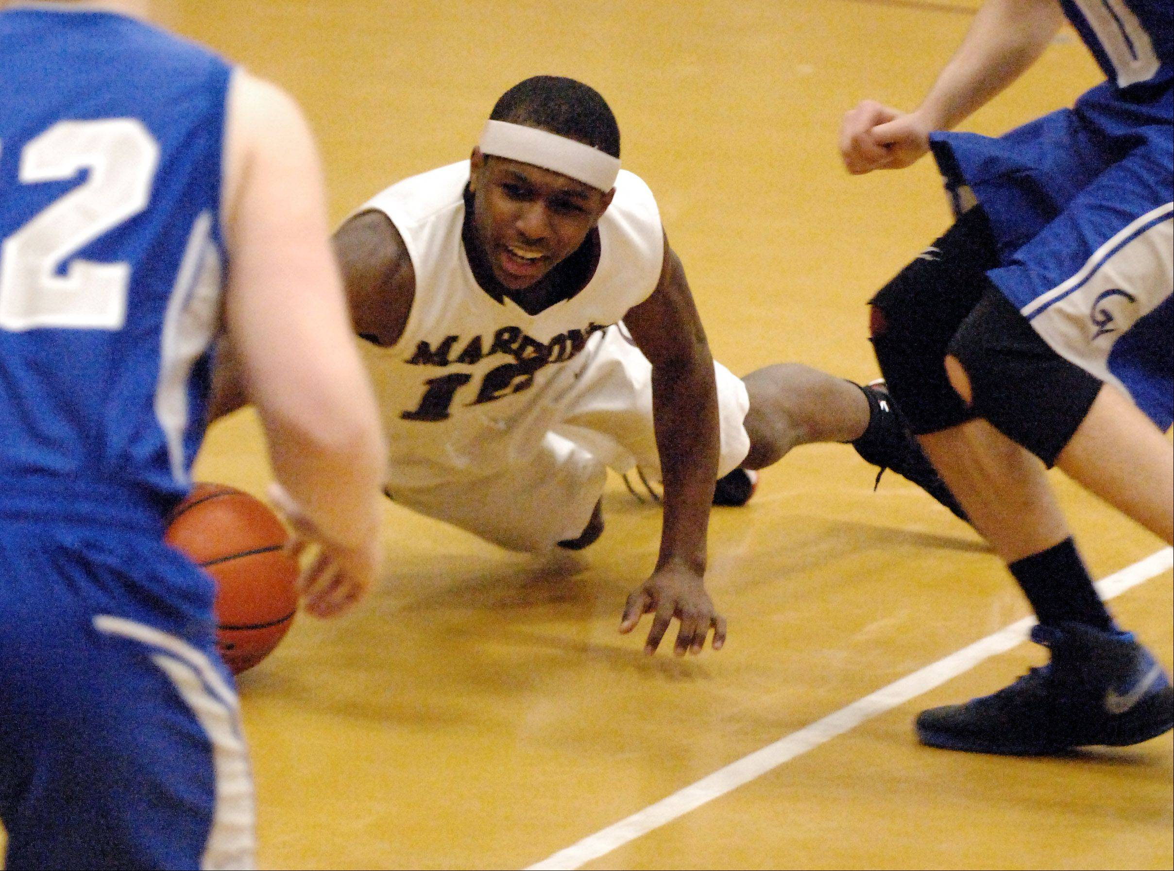 Elgin's Arie Williams dives for a loose ball against Geneva.