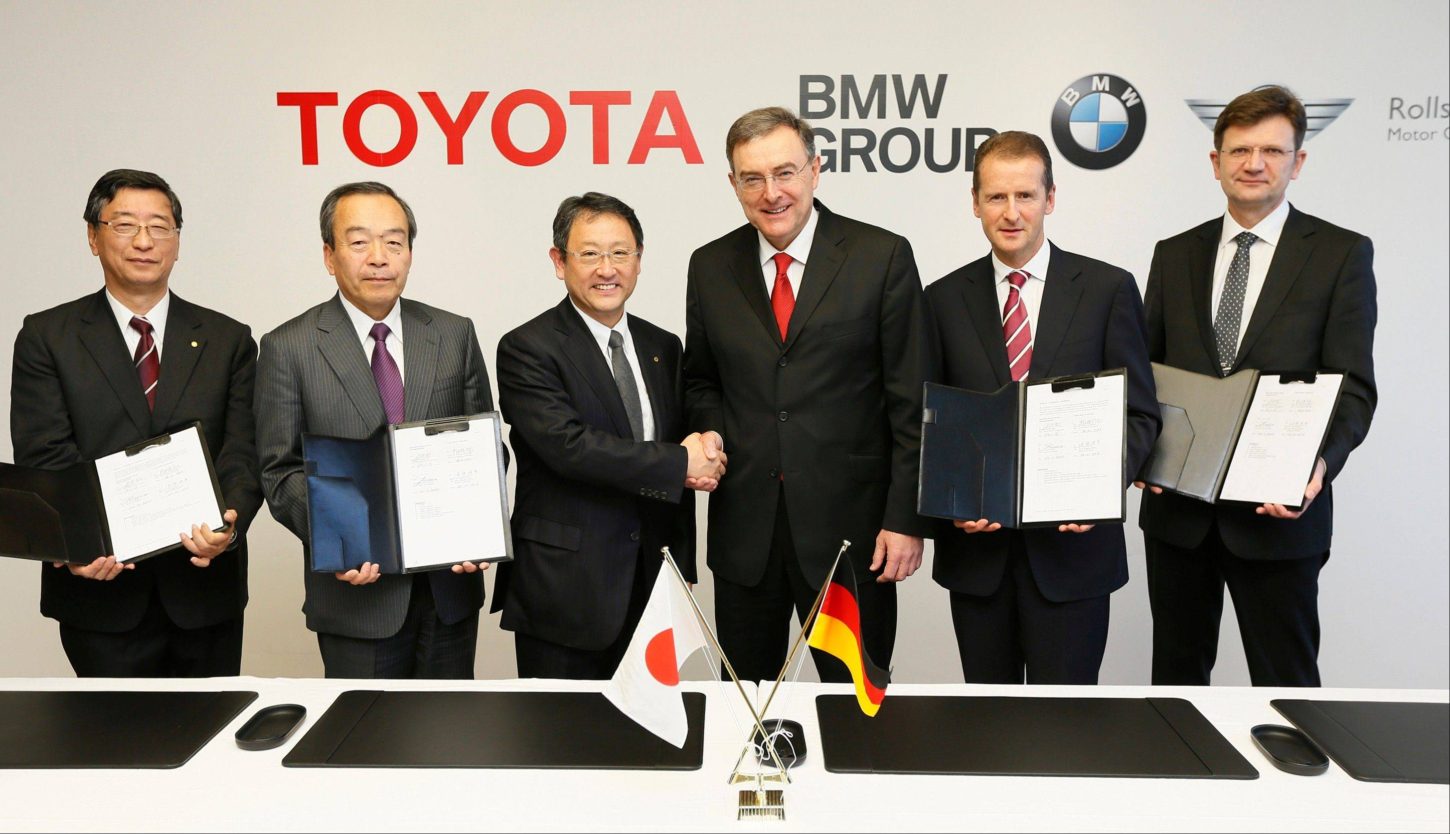 Toyota President Akio Toyoda, third left, shakes hands with BMW AG chief executive Norbert Reithofer, third right, as their executives show signed documents during a signing ceremony to jointly develop next-generation batteries for green vehicles in Nagoya, central Japan, Thursday.