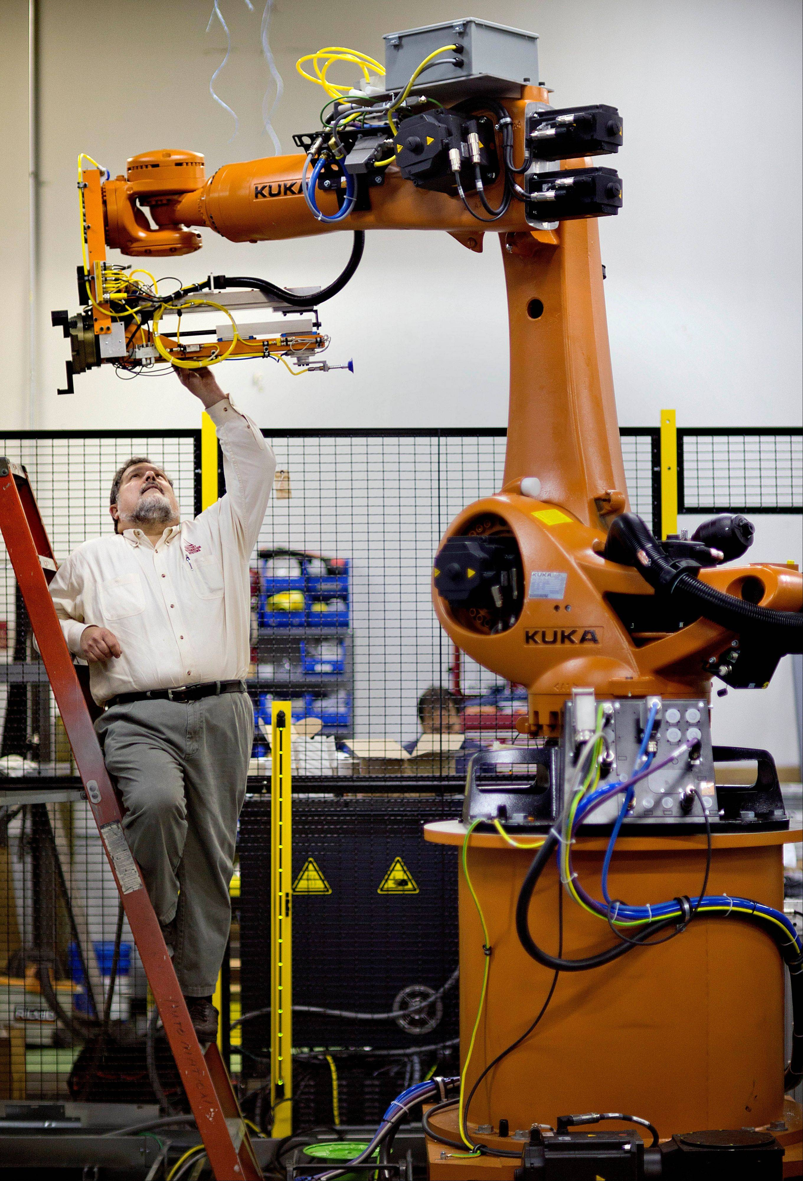 Rosser Pryor, Co-owner and President of Factory Automation Systems, examines a new high-performance industrial robot at the company's Atlanta facility. Pryor, who cut 40 of 100 workers since the recession, says while the company is making more money now and could hire ten people, it is holding back in favor of investing in automation and software.