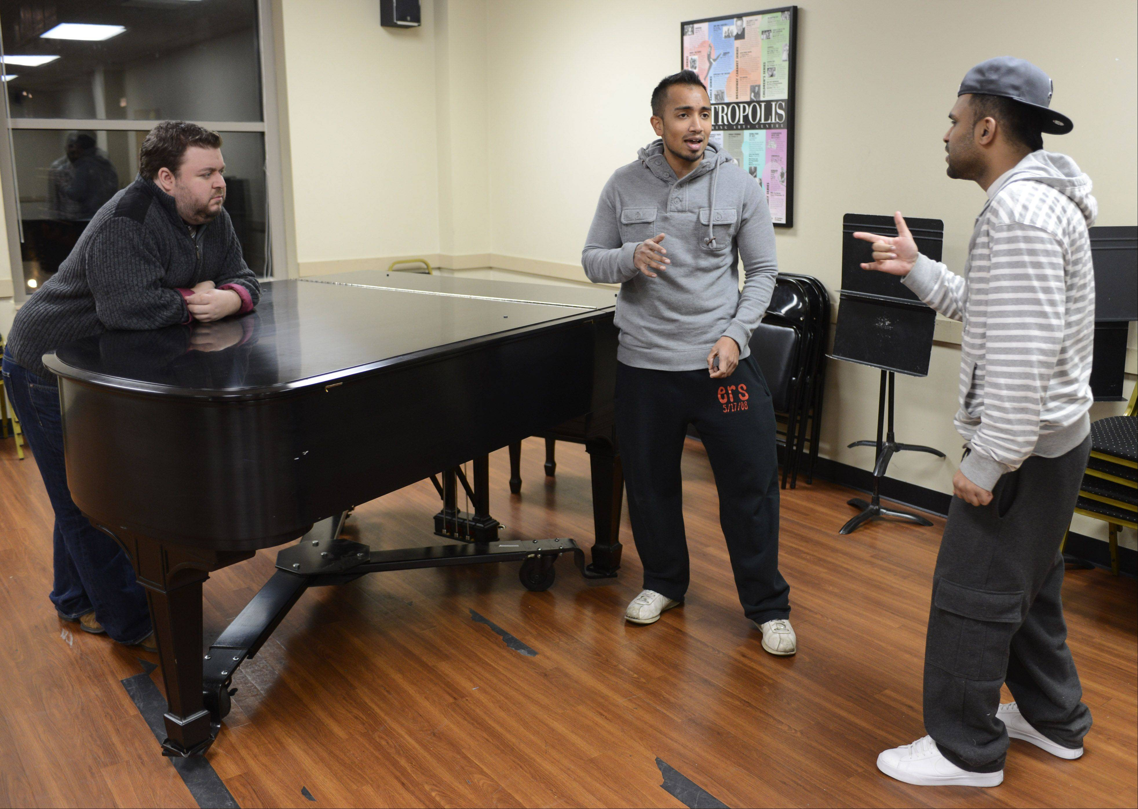 JOE LEWNARD/jlewnard@dailyherald.comShawn Kurian, center, and Sanu John, right, of iLLest Vocals rehearse with Metropolis music director Micky York.