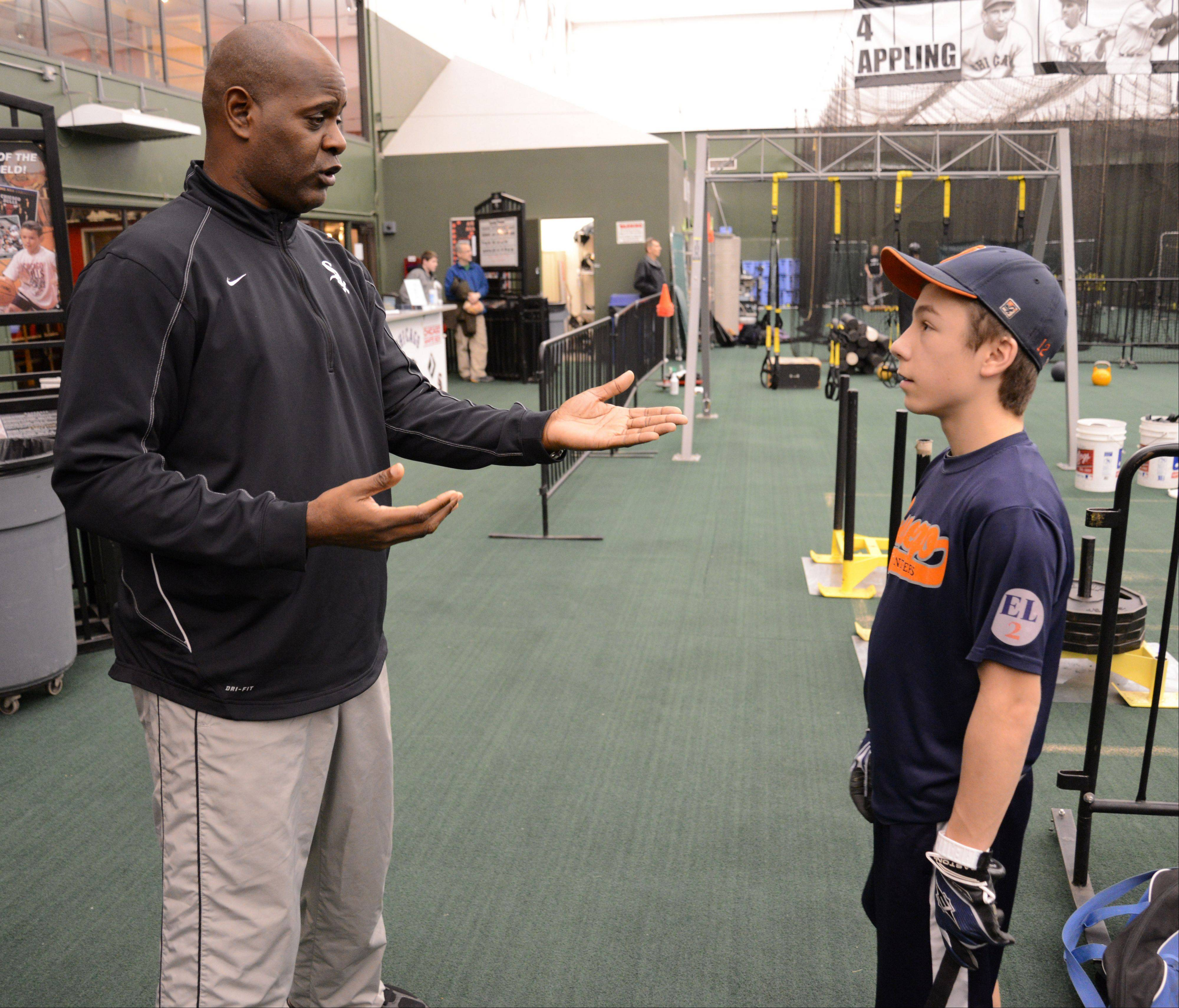 Coach Daryl Boston of the White Sox chats with Mitchell Gwodz, 14, of Oswego during a visit to the Bulls/Sox Academy in Lisle. During a visit Wednesday, Boston watched young players practice and gave them a little coaching.