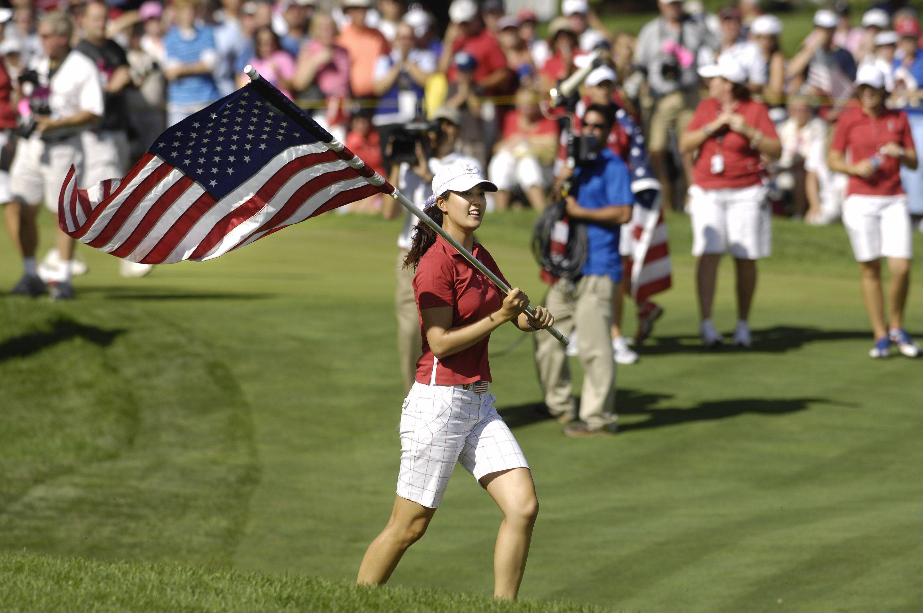 Michelle Wie waves an American Flag after Team USA defeated Europe at the final round of the Solheim Cup in Sugar Grove in 2009. The Solheim Cup drew more than 120,000 fans to the biennial competition.