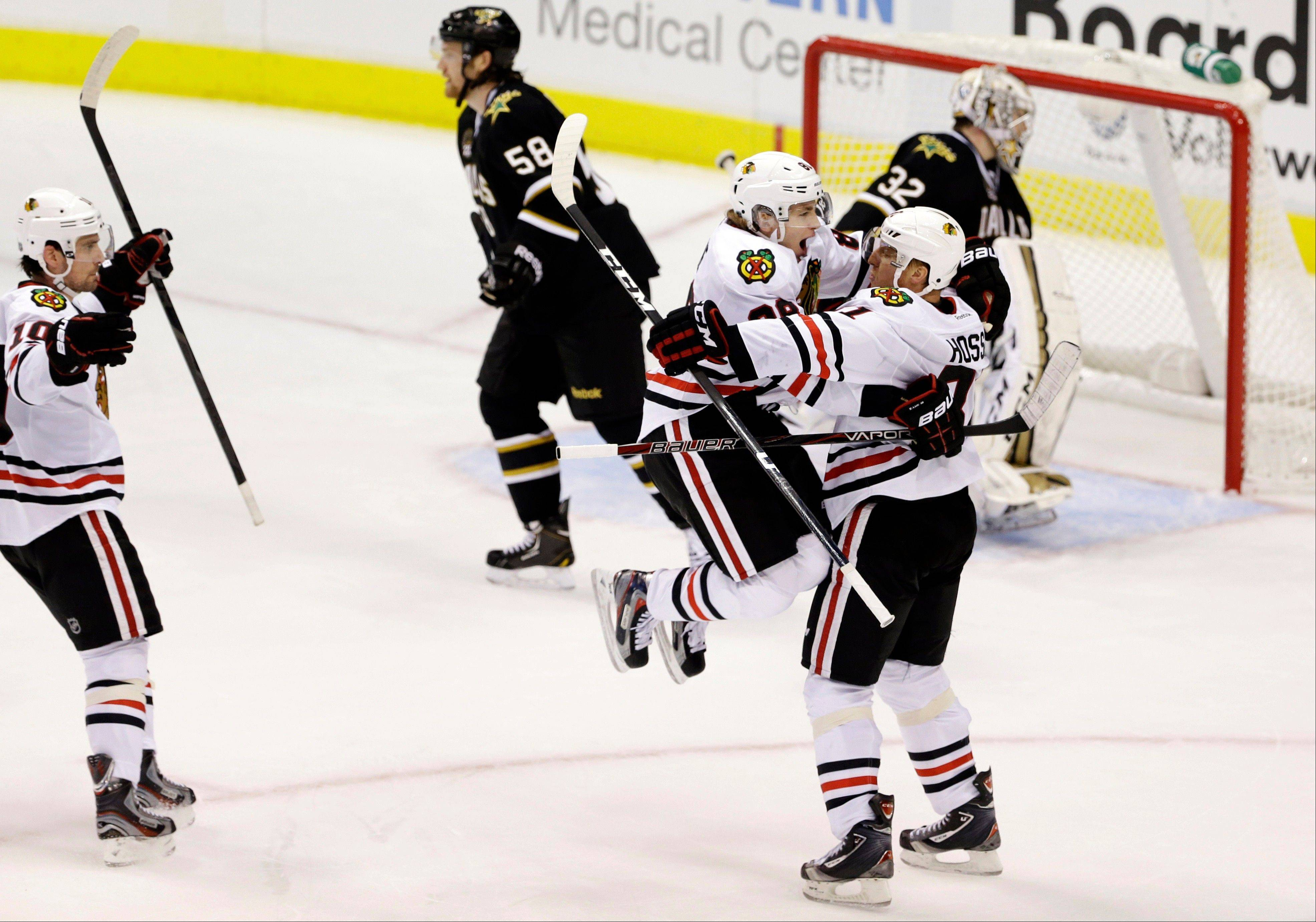 Patrick Sharp, left, watches as Patrick Kane, center left, and Marian Hossa (81), celebrate Hossa's overtime goal against Dallas Stars goalie Kari Lehtonen on Thursday night.
