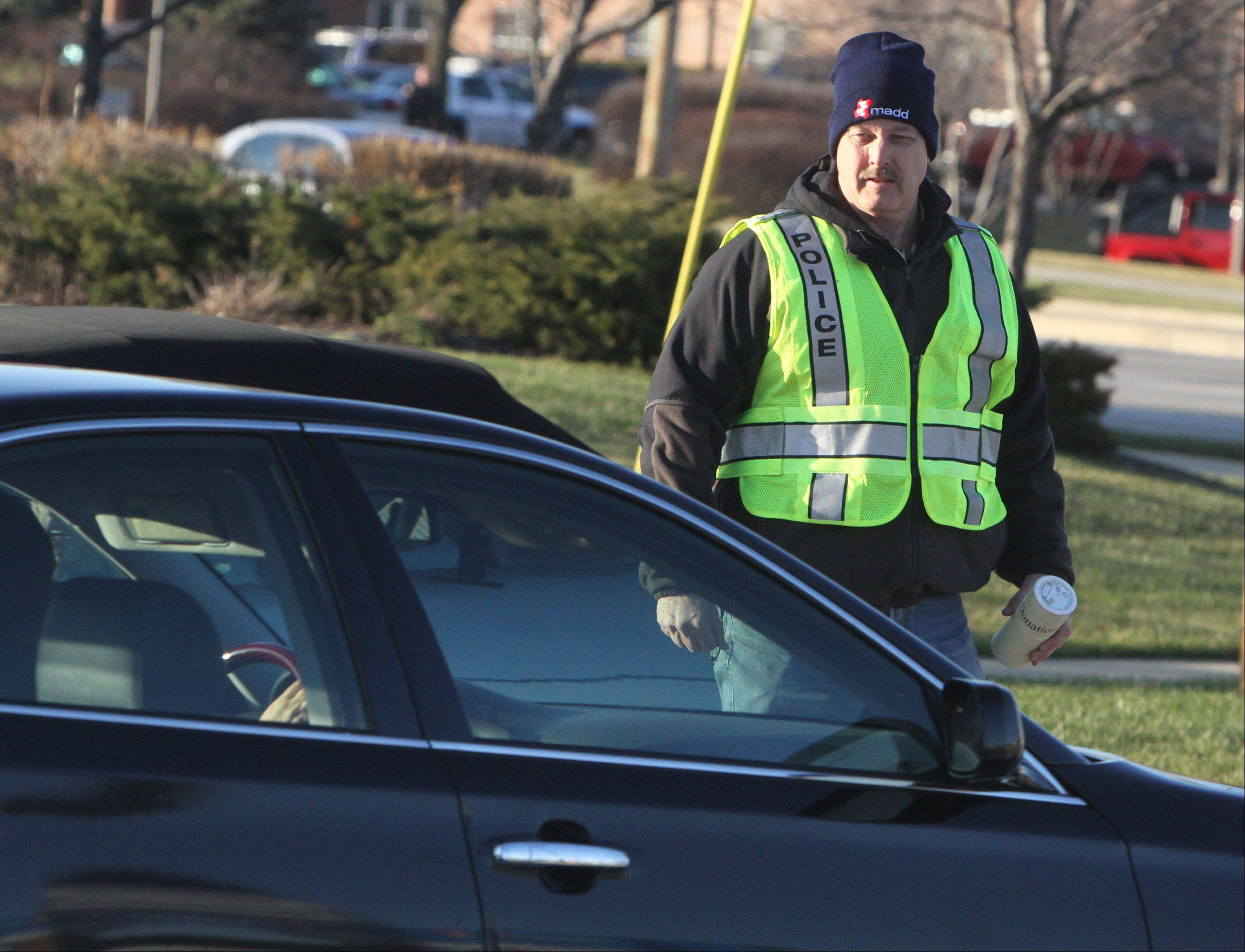 Sgt. Scott Kristiansen poses as a solicitor as he checks to see if drivers are using mobile devices while driving north through the intersection of Arlington Heights Road and Rt. 83 in Buffalo Grove. Kristiansen used unorthodox tactics to boost safety.
