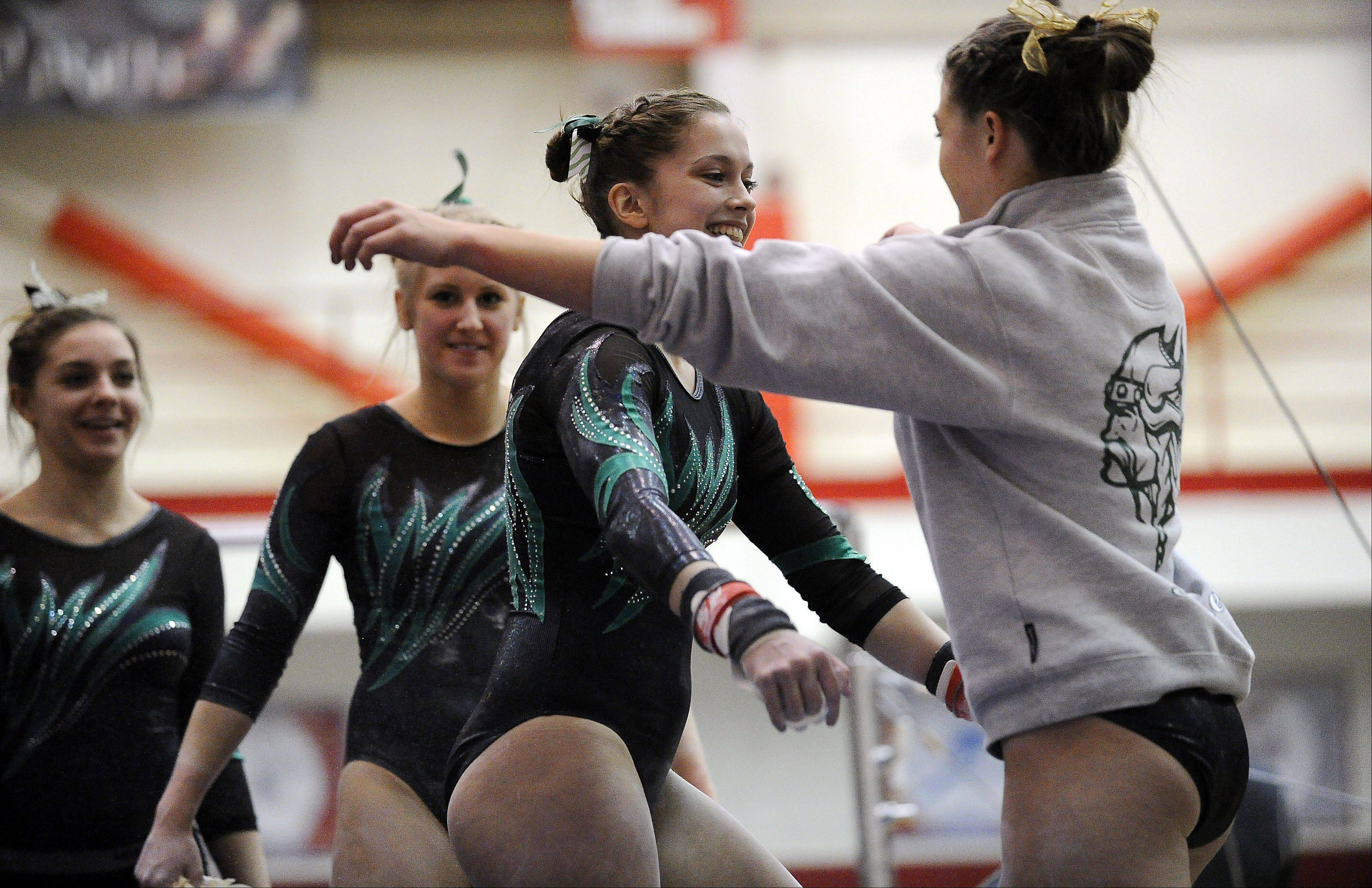 Fremd�s Emily Pinderski is congratulated by her teammates after her performance on the uneven parallel bars at the Mid-Suburban League meet at Palatine on Friday.