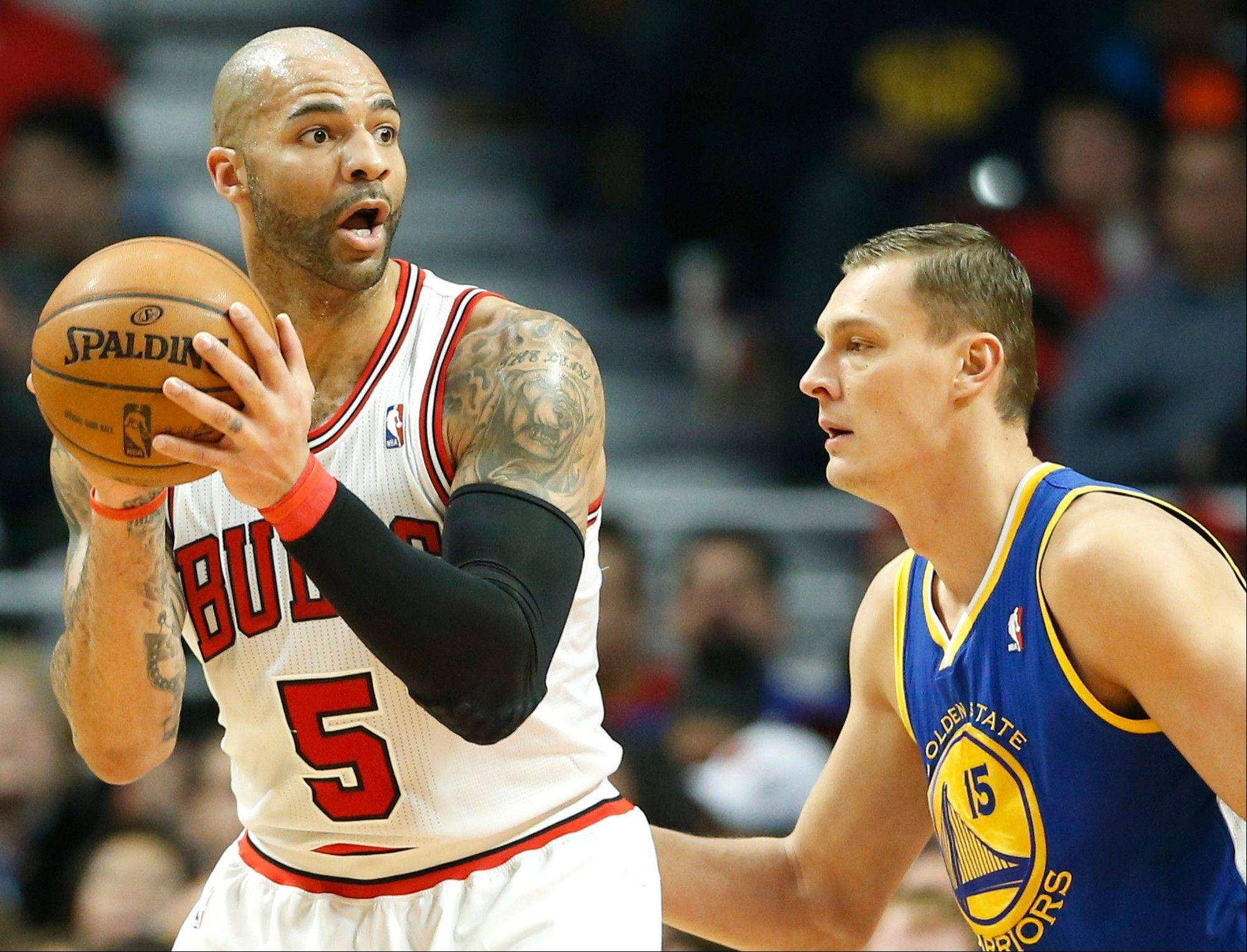 Carlos Boozer, left, looks to a pass against Golden State Warriors center Andris Biedrins, of Latvia, during the first half of an NBA basketball game in Chicago on Friday, Jan. 25, 2013. The Bulls won 103-87.