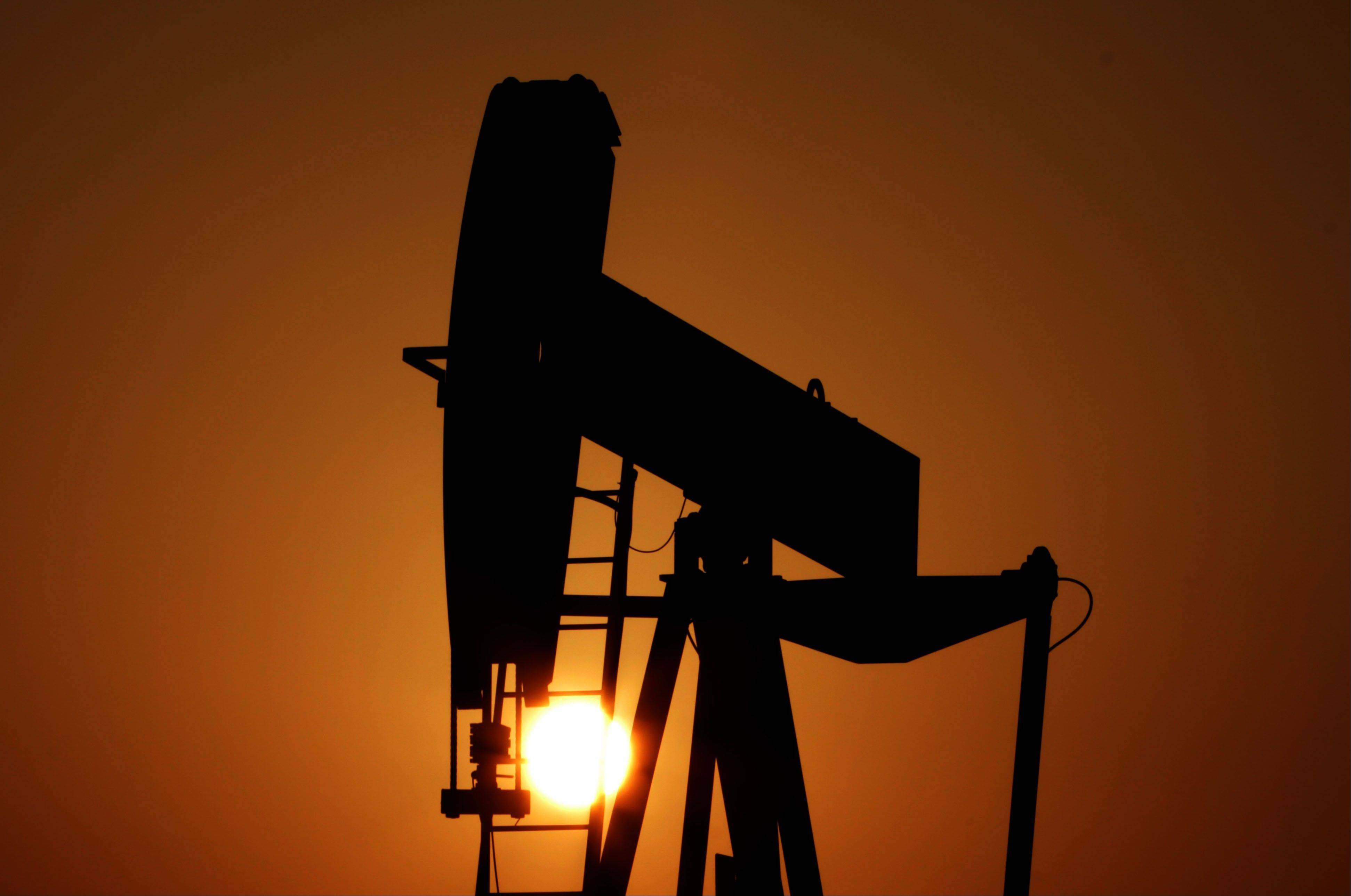 An oil pump works at sunset in the desert oil fields of Sakhir, Bahrain.