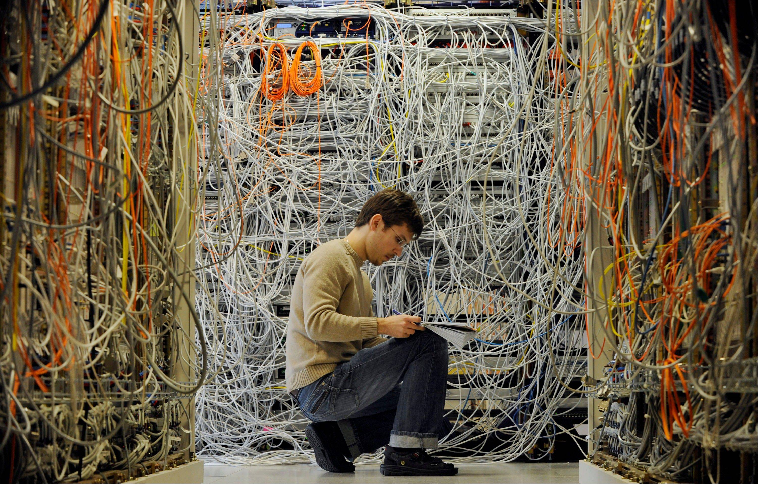 An engineer checks communication cables in the Media Gateway (MGW) lab simulating translation between disparate telecommunications networks, in Ericsson's research and development center in Budapest, Hungary.