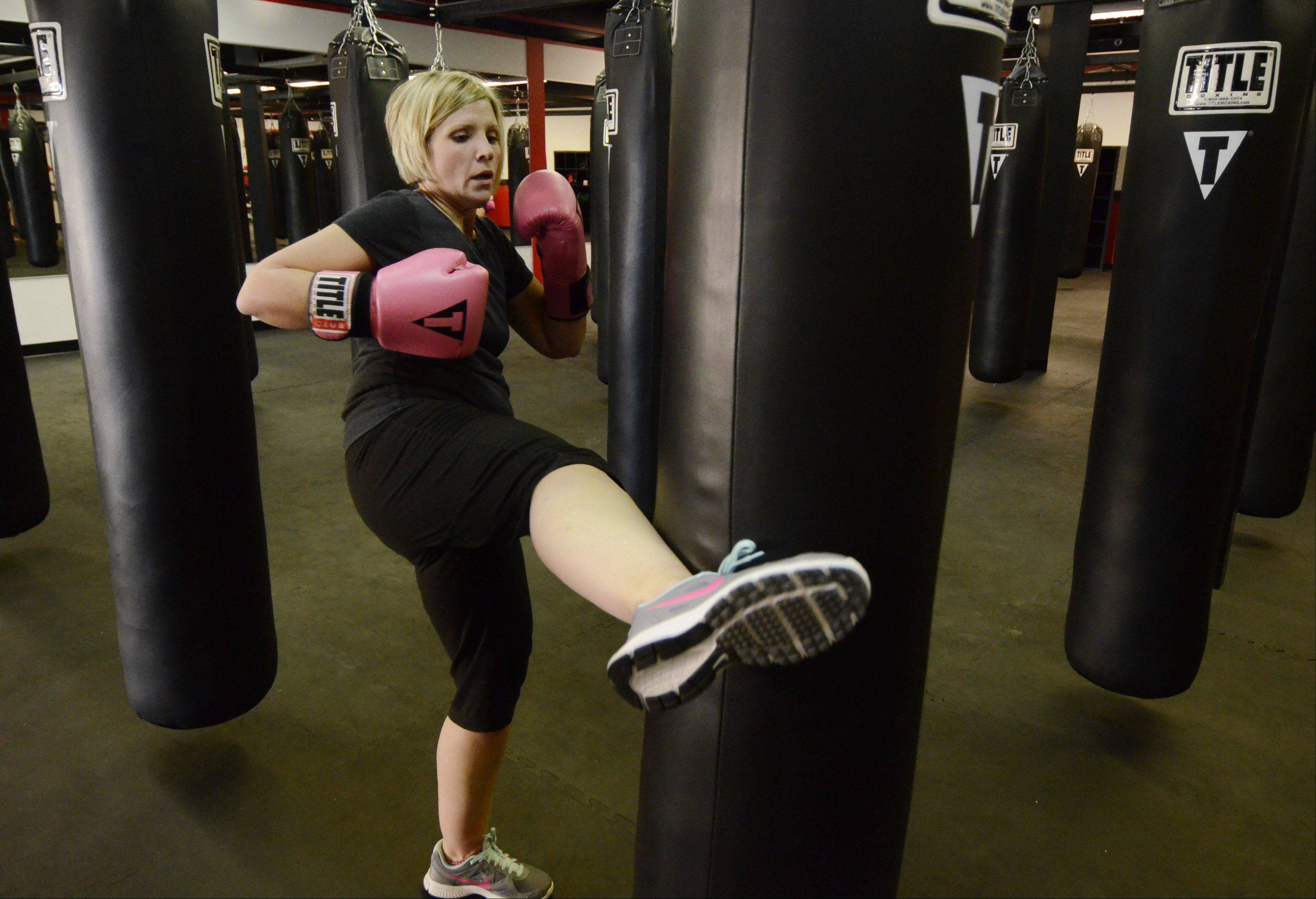 Erin Alsakhria, the mother of two boys, works out during the Power Hour class at Title Boxing Club in Schaumburg.