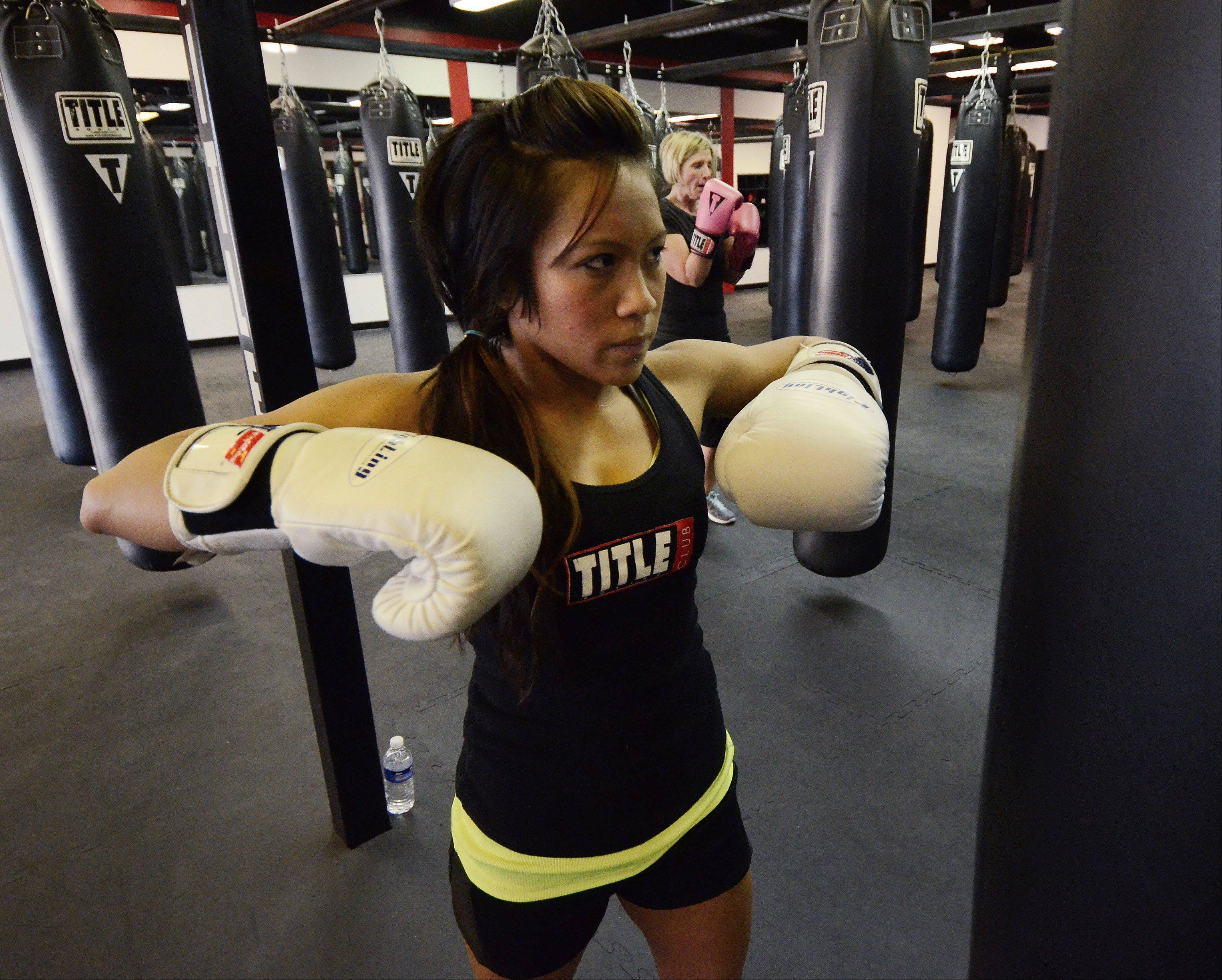 Title Boxing Club trainer Cher Nicolas gets ready to lead a workout.