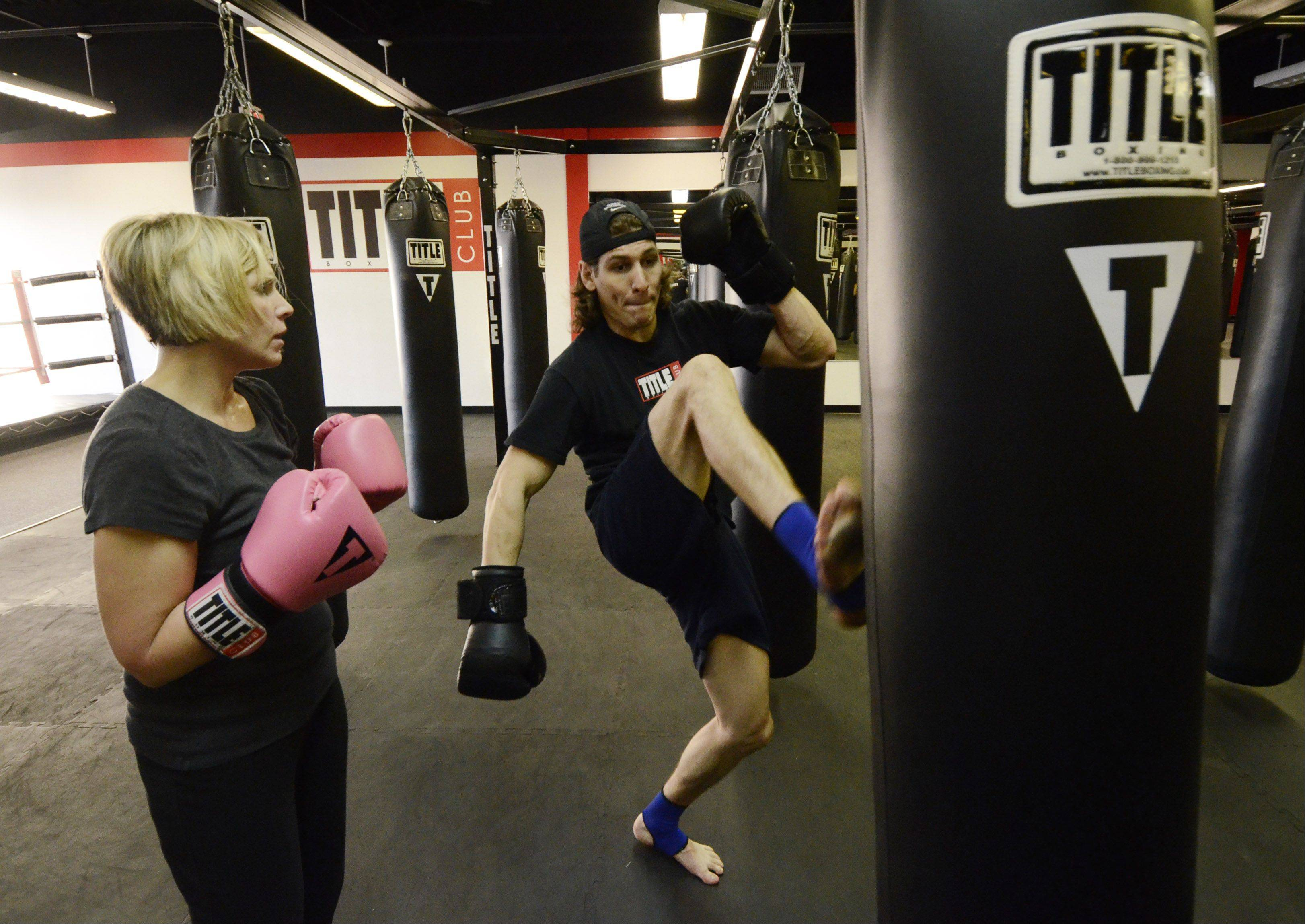 Mother-of-two Erin Alsakhria listens to trainer Sammy Horowitz during a workout at Title Boxing Club in Schaumburg.