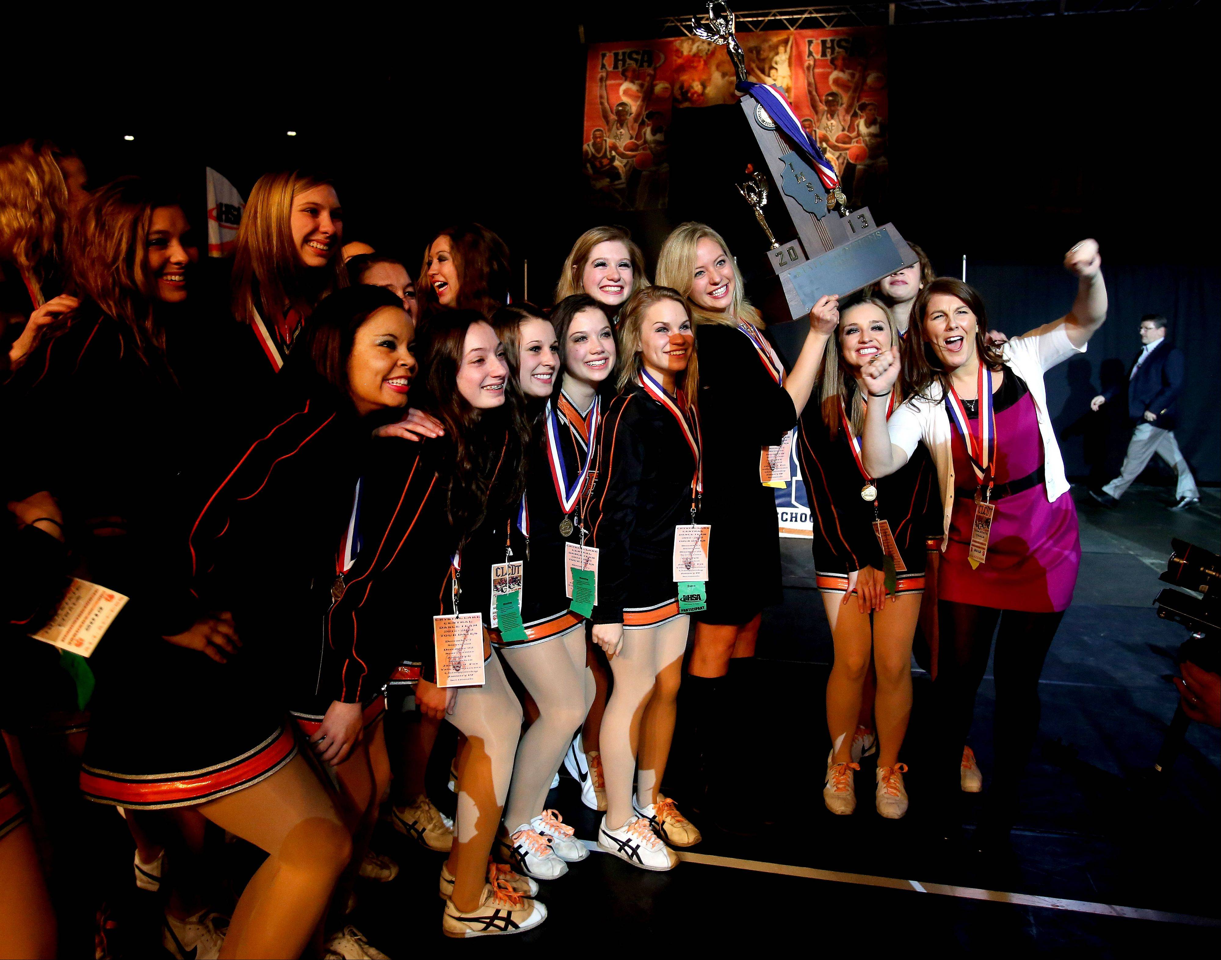 Crystal Lake Central coach Caroline Christensen holds the trophy as the team poses for a photo after their first place finish in the 2A division of the Competitive Dance State Finals on Saturday in Bloomington.