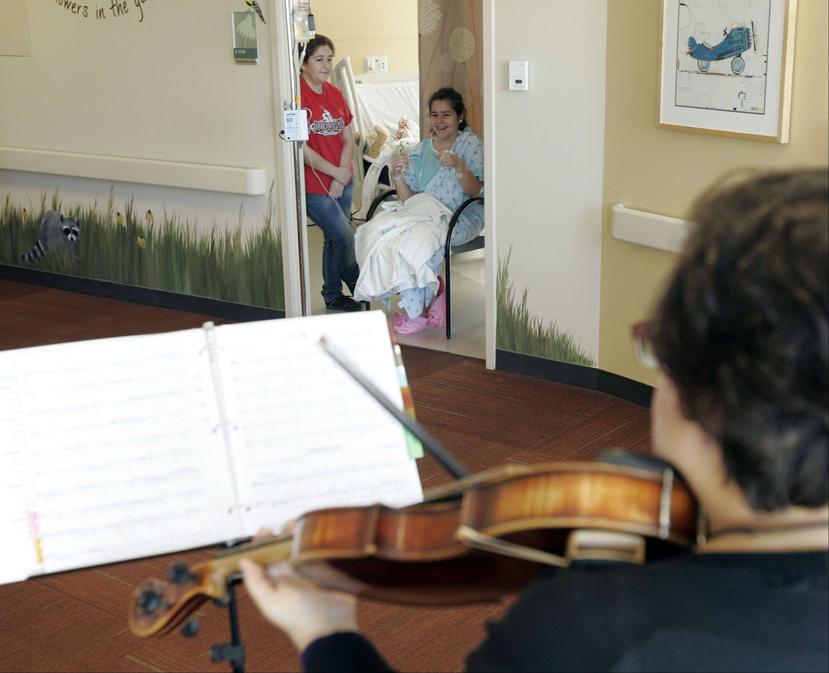 "Elgin Symphony Orchestra violist Loretta Gillespie plays tunes from ""Mary Poppins"" on the viola as Penelope Garcia and her 14-year-old daughter, Brooke Mora, of Elgin, listen from Brooke's room at Sherman Hospital."