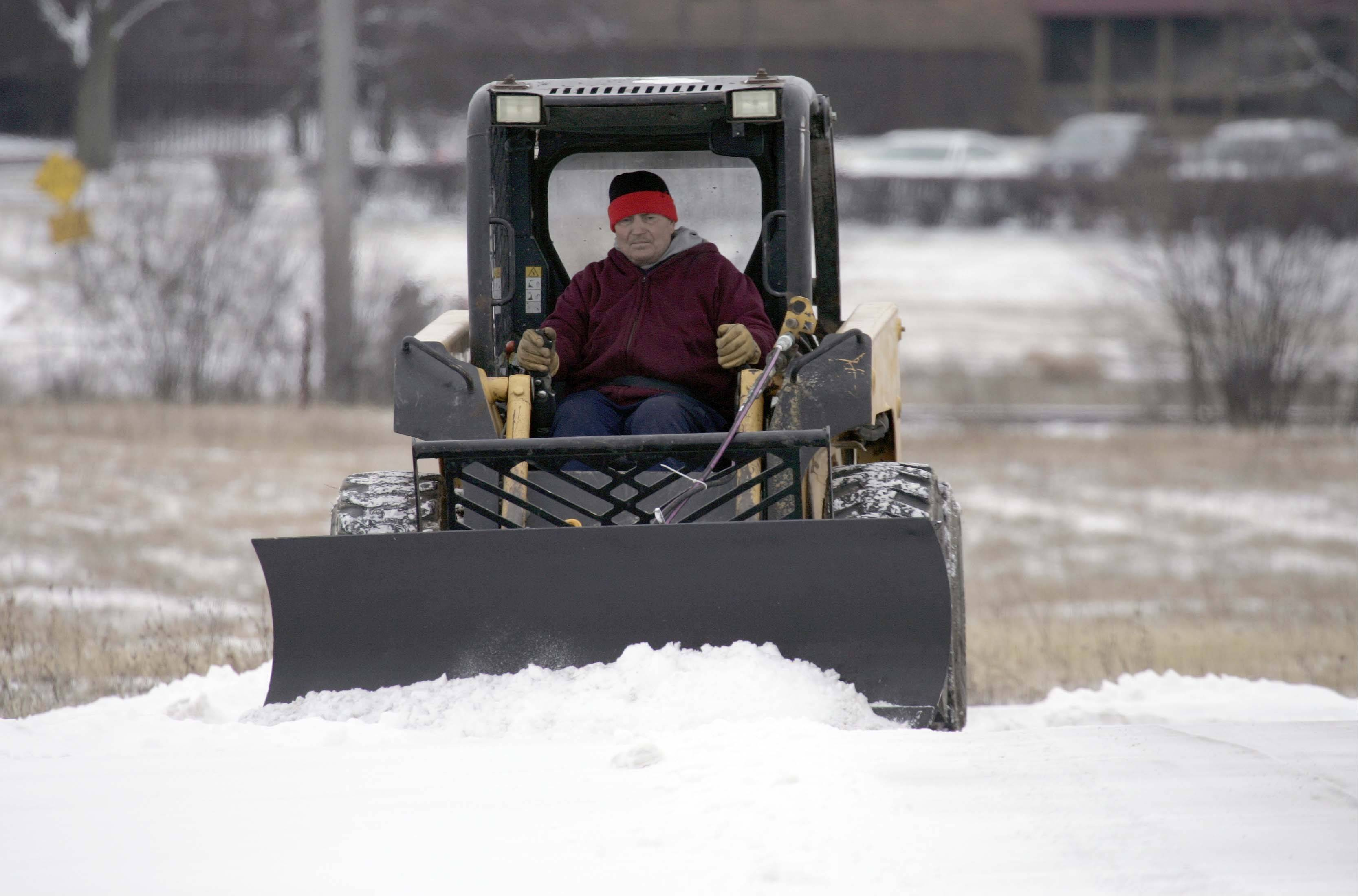 Mike Stalka of Amaya out of Aurora clears snow at the Foundry Business Park in St. Charles after a minimal snowfall early Friday morning.