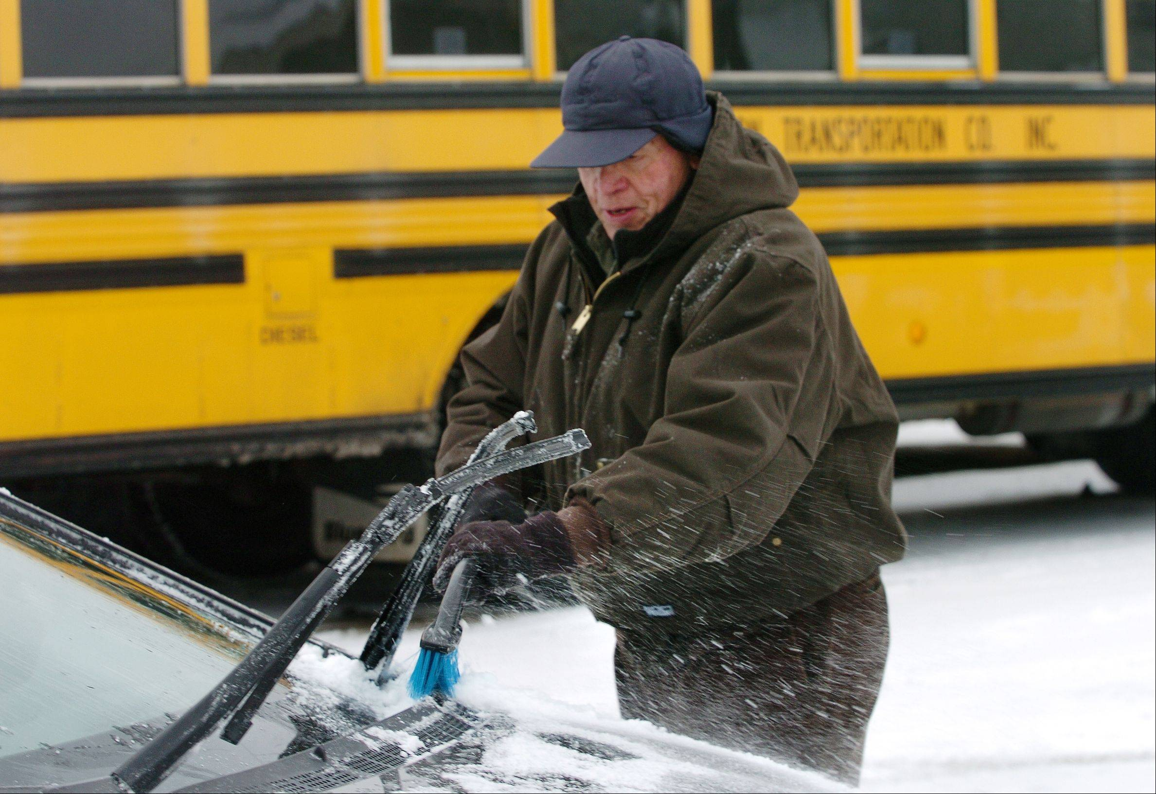 School bus driver Clint Curtis brushes off his car after finishing his morning run Friday in Barrington.