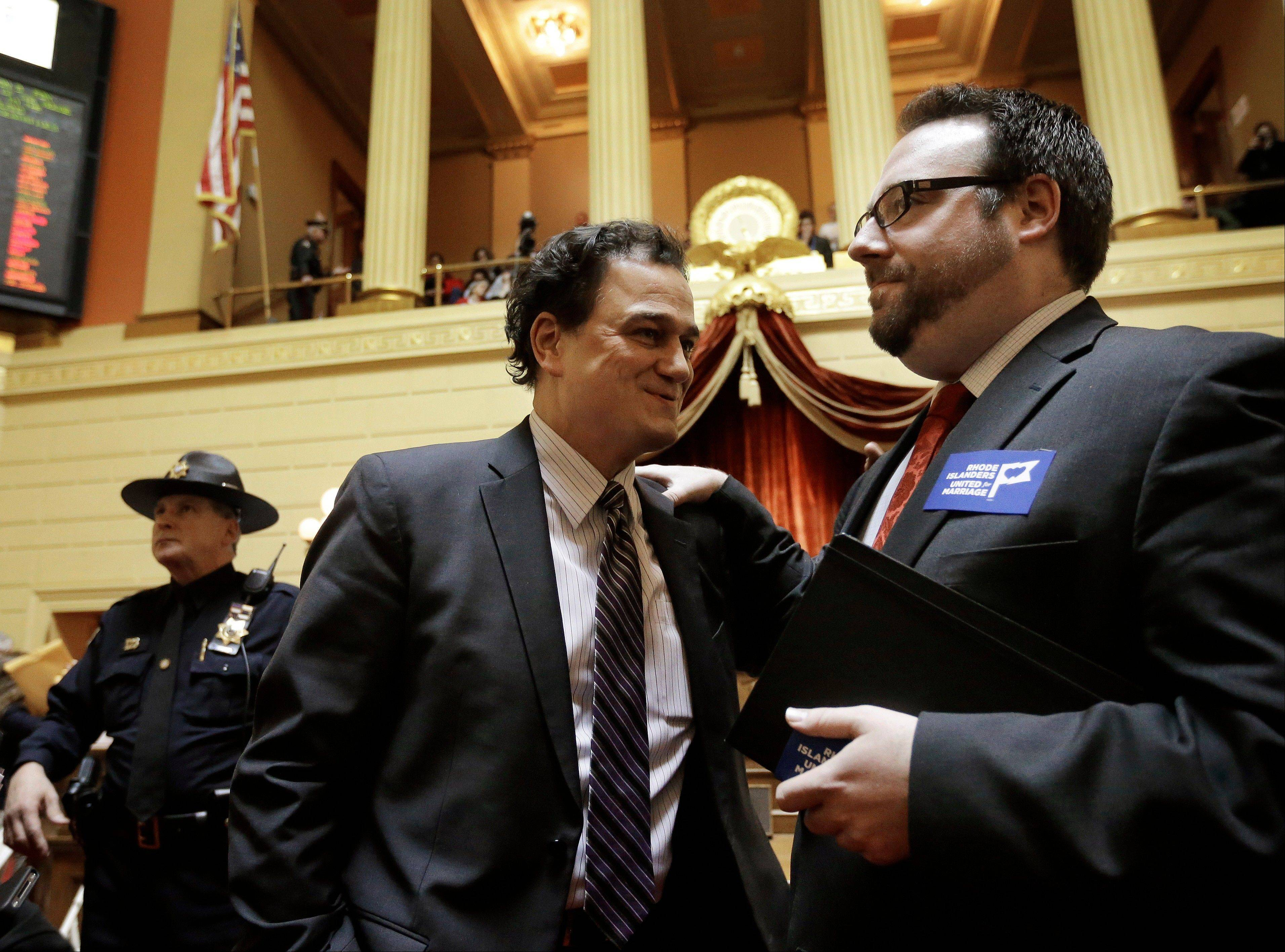 Rhode Island speaker of the House Gordon Fox, center, speaks with Ray Sullivan, campaign director for Rhode Islanders United for Marriage, right, in the House Chamber at the Statehouse, in Providence, R.I., Thursday, Jan. 24, 2013. Legislation to allow gay marriage in the state passed a House vote Thursday.