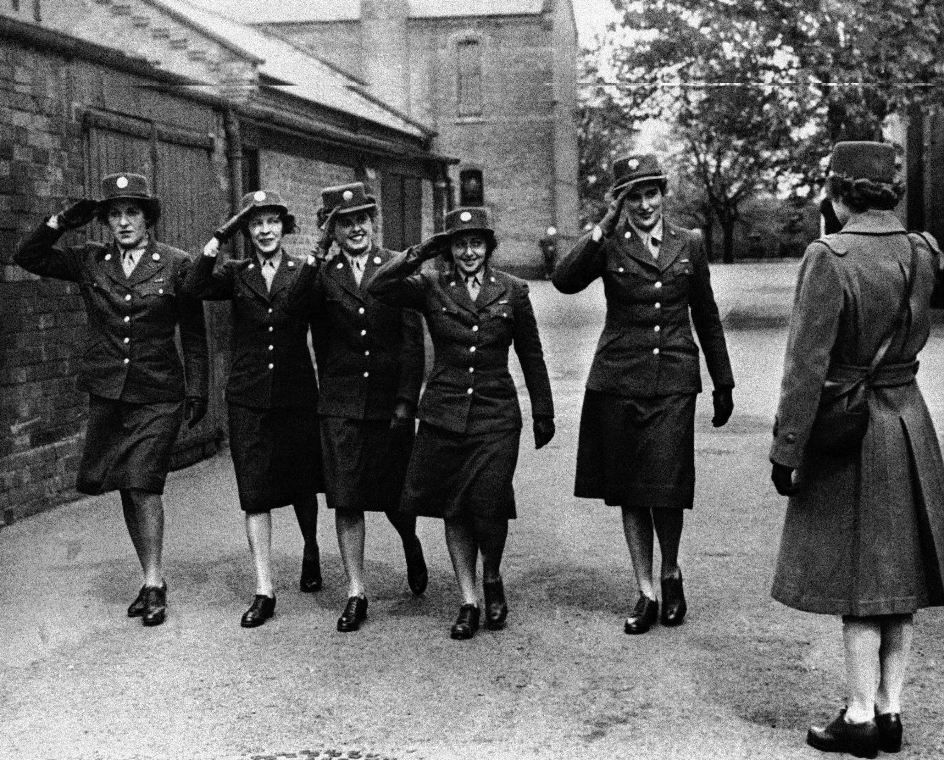 May 5, 1944: Five members of the Women's Army Corps serving with the army service of supplies, salute an officer at a base in England.