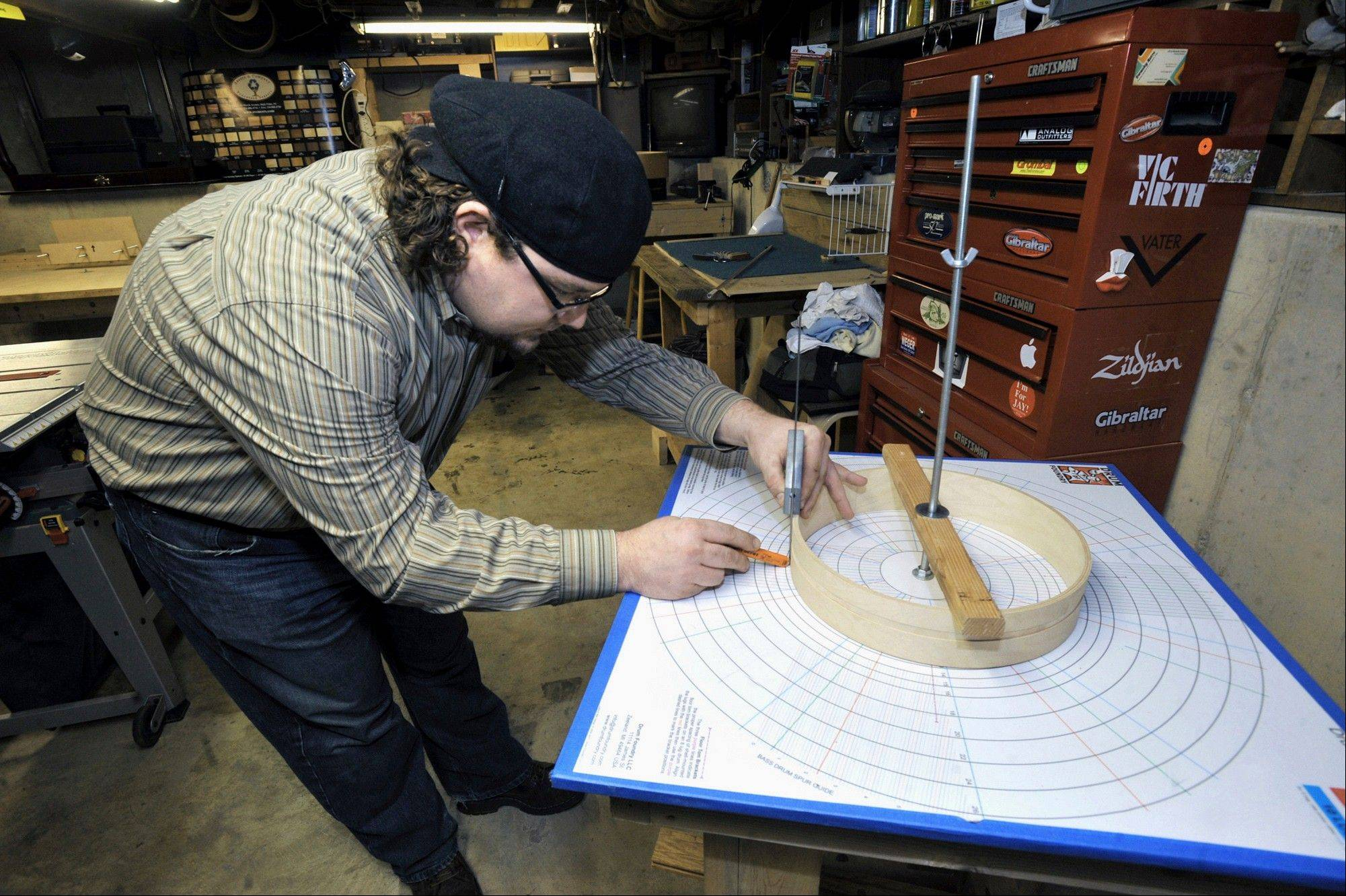 Drum maker Jay Ferguson demonstrates the use of the drum shell layout table in the workshop.