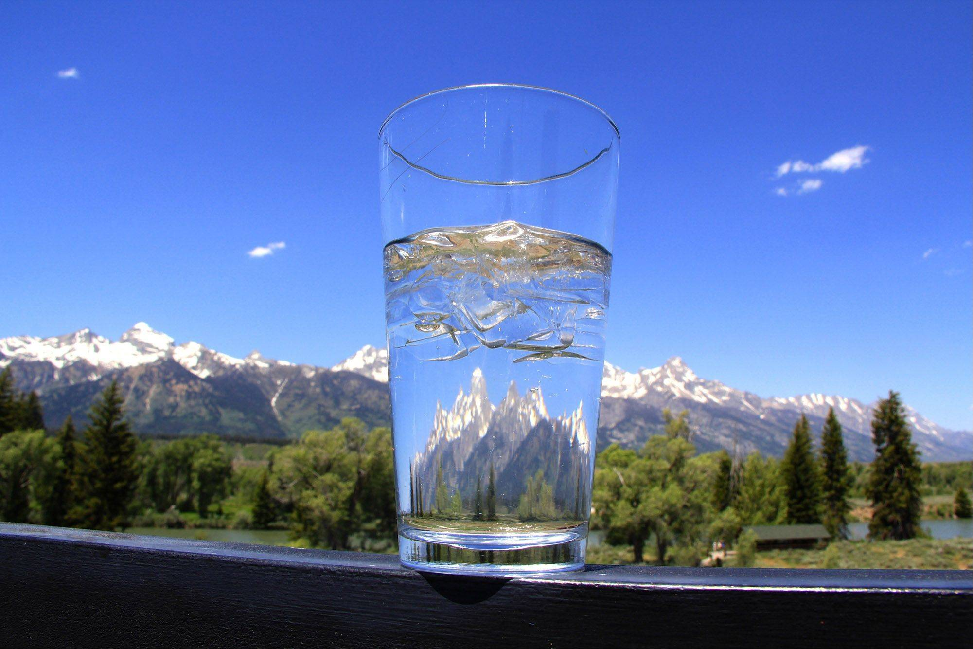 The Grand Teton mountains are reflected in a glass on the balcony of a restaurant overlooking the Teton range last June on a beautiful Wyoming day.