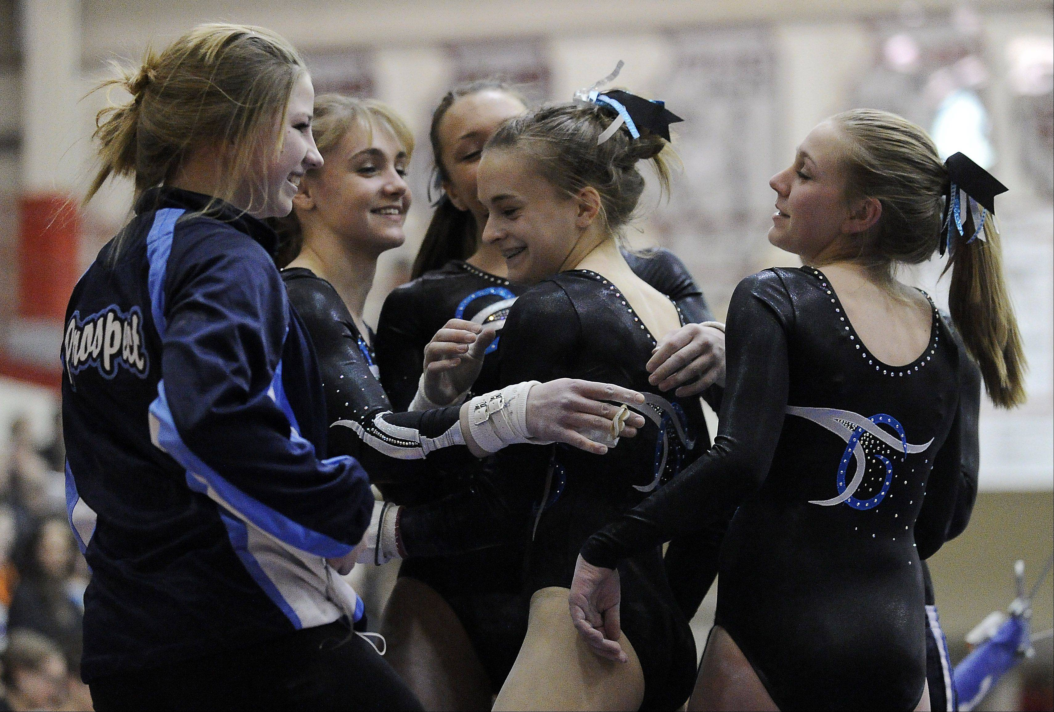 Prospect's Maddie Larock (center) is congratulated by her teammates after her performance on the uneven parallel bars at the Mid-Suburban League meet at Palatine on Friday.