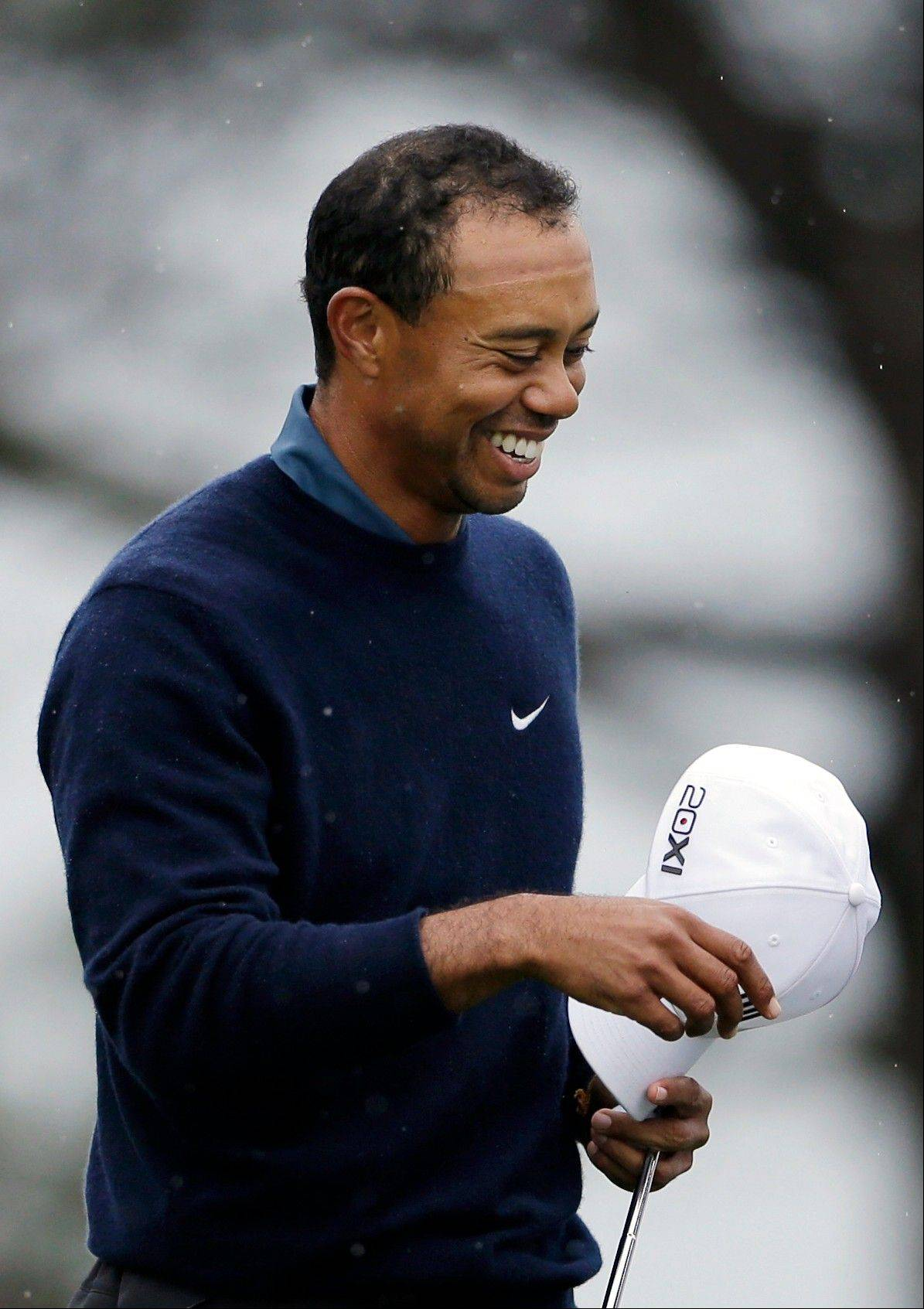 Tiger Woods smiles as he waits to hit his second shot on the seventh hole of the north course at the Torrey Pines Golf Course during the second round of the Farmers Insurance Open golf tournament Friday, Jan. 25, 2013, in San Diego.