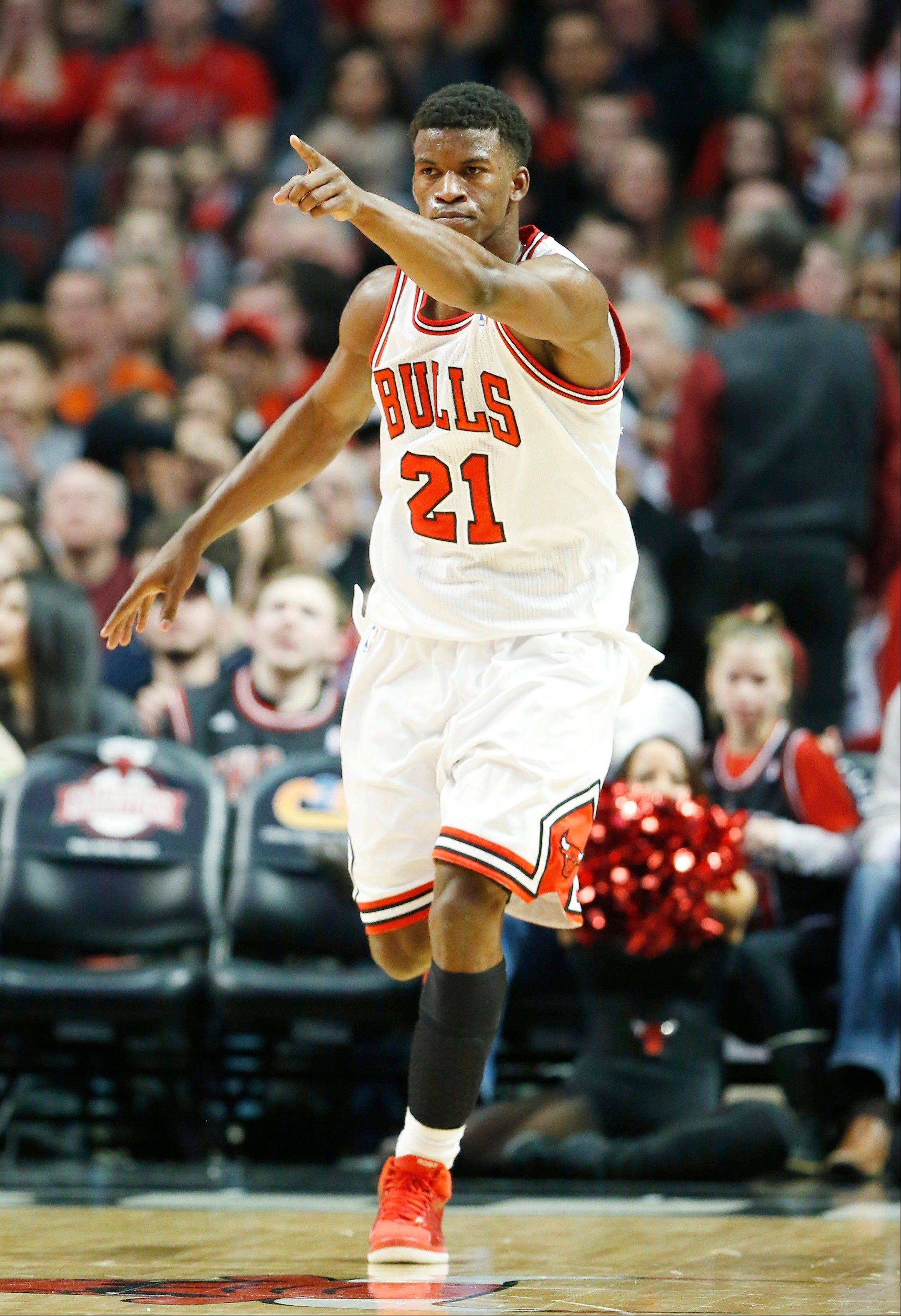 Jimmy Butler points as he celebrates after scoring a basket during the first half of an NBA basketball game against the Golden State Warriors in Chicago on Friday, Jan. 25, 2013. The Bulls won 103-87.