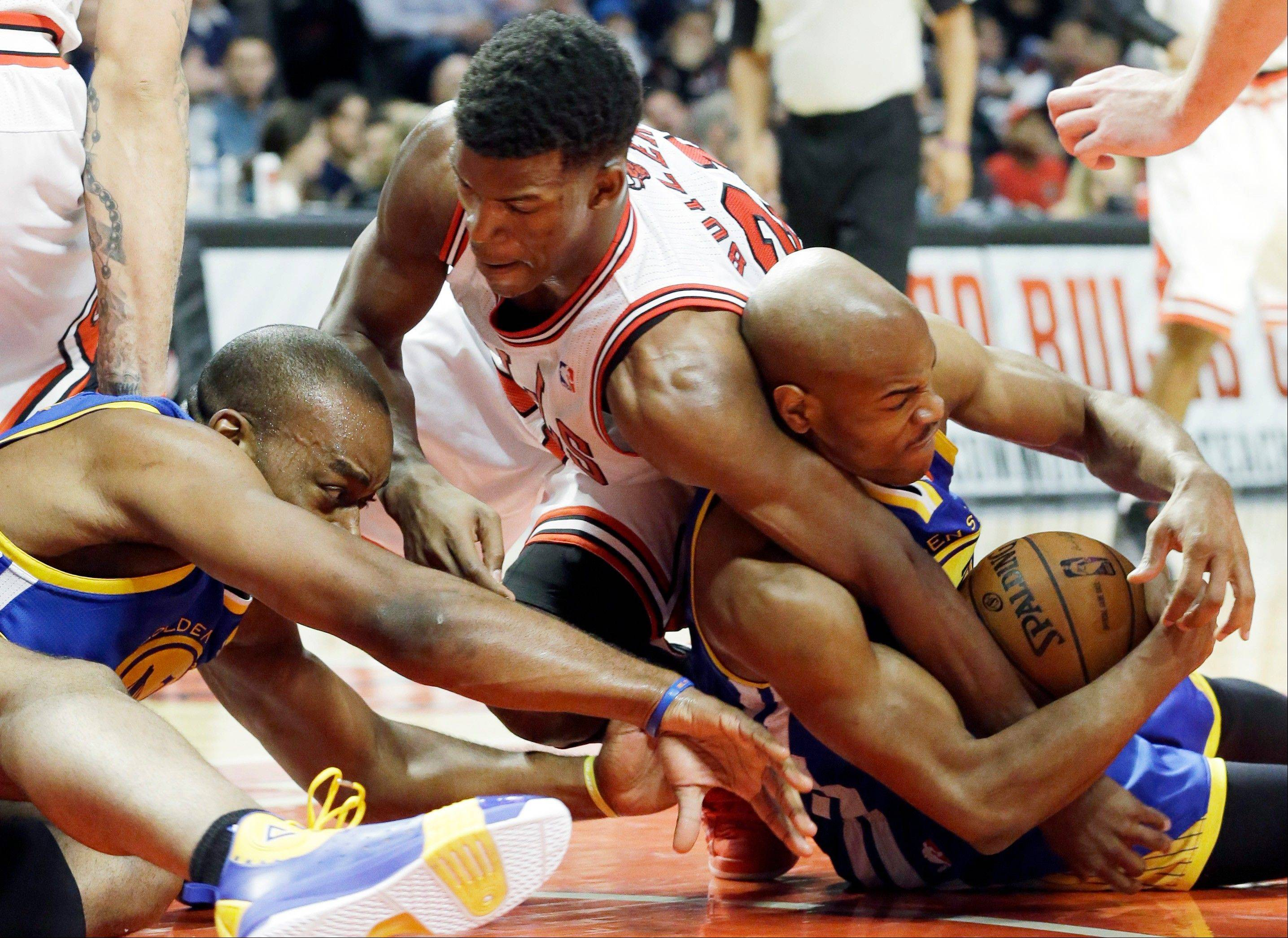 Jimmy Butler, center, battles for a loose ball with Golden State Warriors forward Carl Landry, left, and guard Jarrett Jack during the second half of an NBA basketball game in Chicago on Friday, Jan. 25, 2013. The Bulls won 103-87.