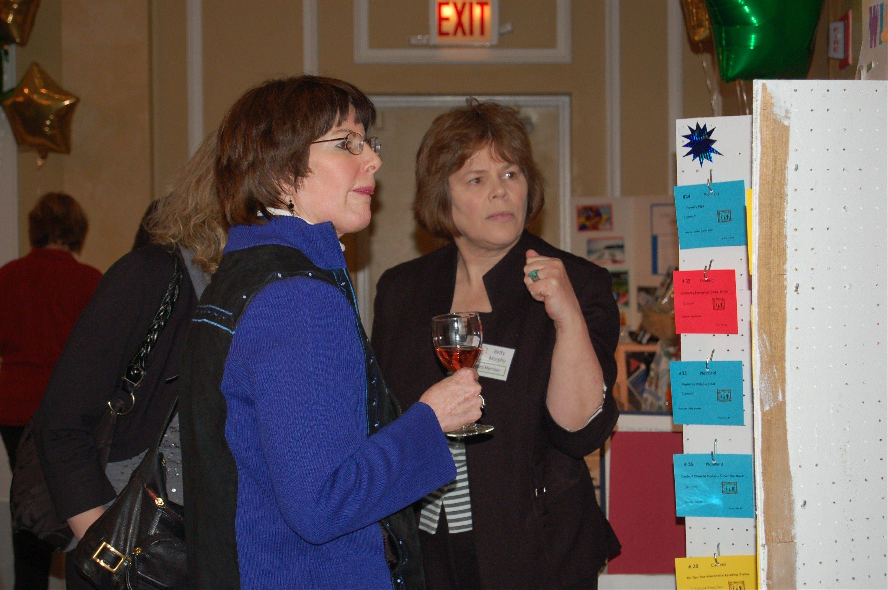 Jean Wilson, retired Cumberland Elementary School teacher, and Betty Murphy, Reach to Teach Benefit co-chairman, discuss what they will bid on at the D62 Foundation Reach to Teach Benefit. All proceeds provide learning opportunities for D62 students.