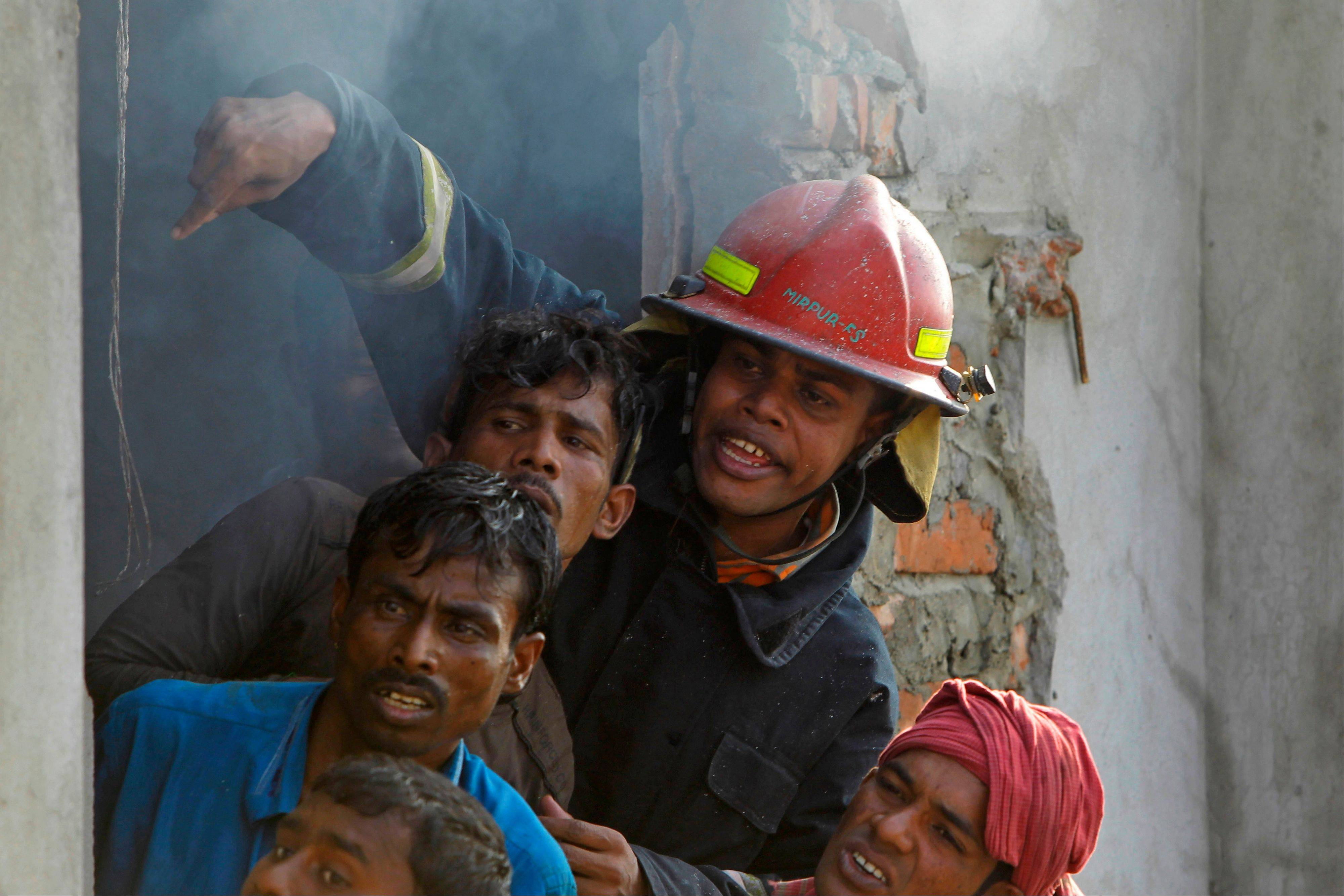 Bangladeshi firefighters and volunteers work to douse a fire at a two-storied garment factory in Dhaka, Bangladesh, Saturday, Jan.26, 2013. The fire killed at least six female workers and injured another five, police and fire officials said. The latest fire occurred more than two months after a deadly fire killed 112 workers in another factory near the capital city, raising questions about the safety measures in Bangladesh garment industry.