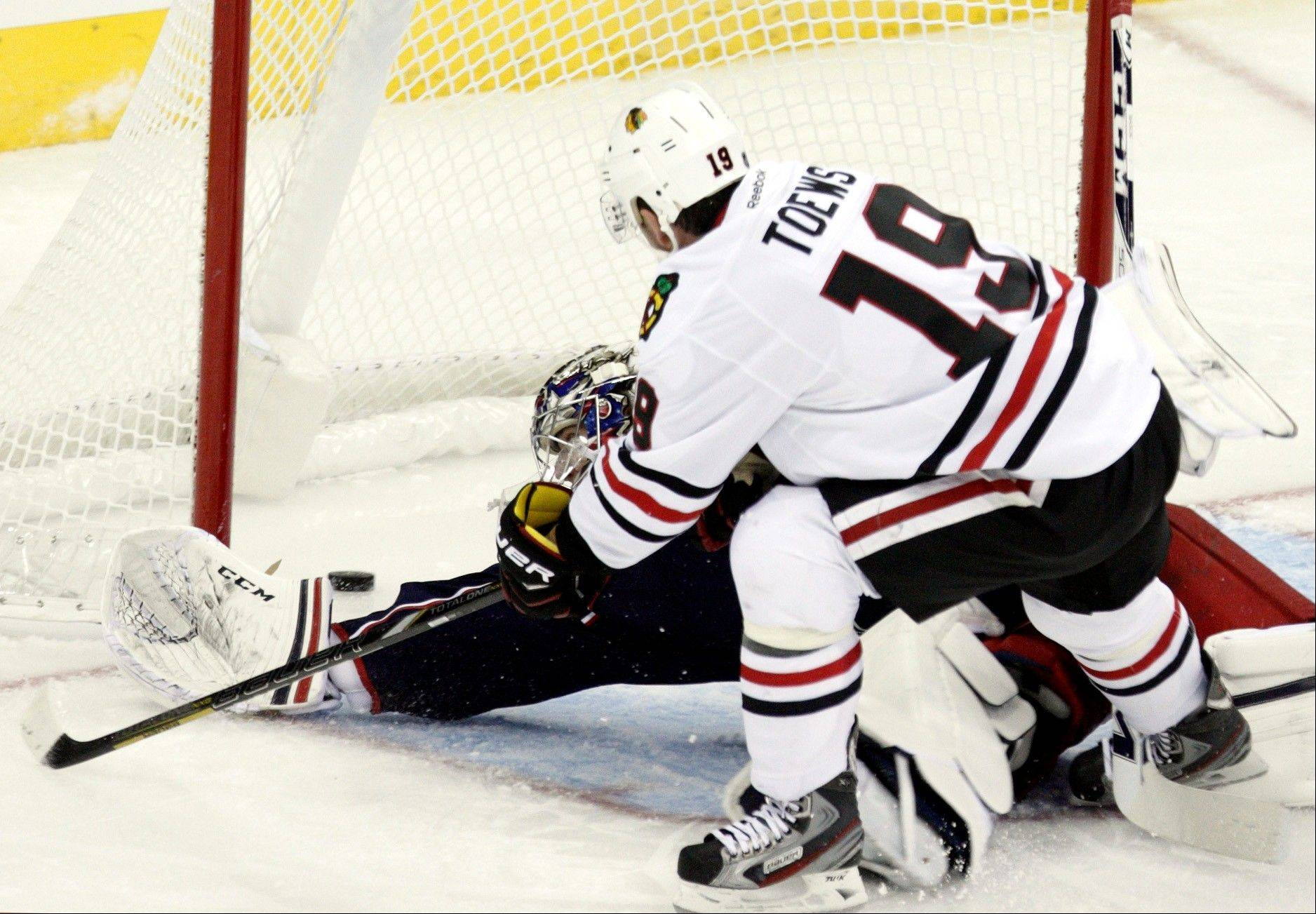 Chicago Blackhawks center Jonathan Toews, right, slips the puck past against Columbus Blue Jackets� Steve Mason in the third period of an NHL hockey game in Columbus, Ohio, Saturday, Jan. 26, 2013. Chicago won 3-2.