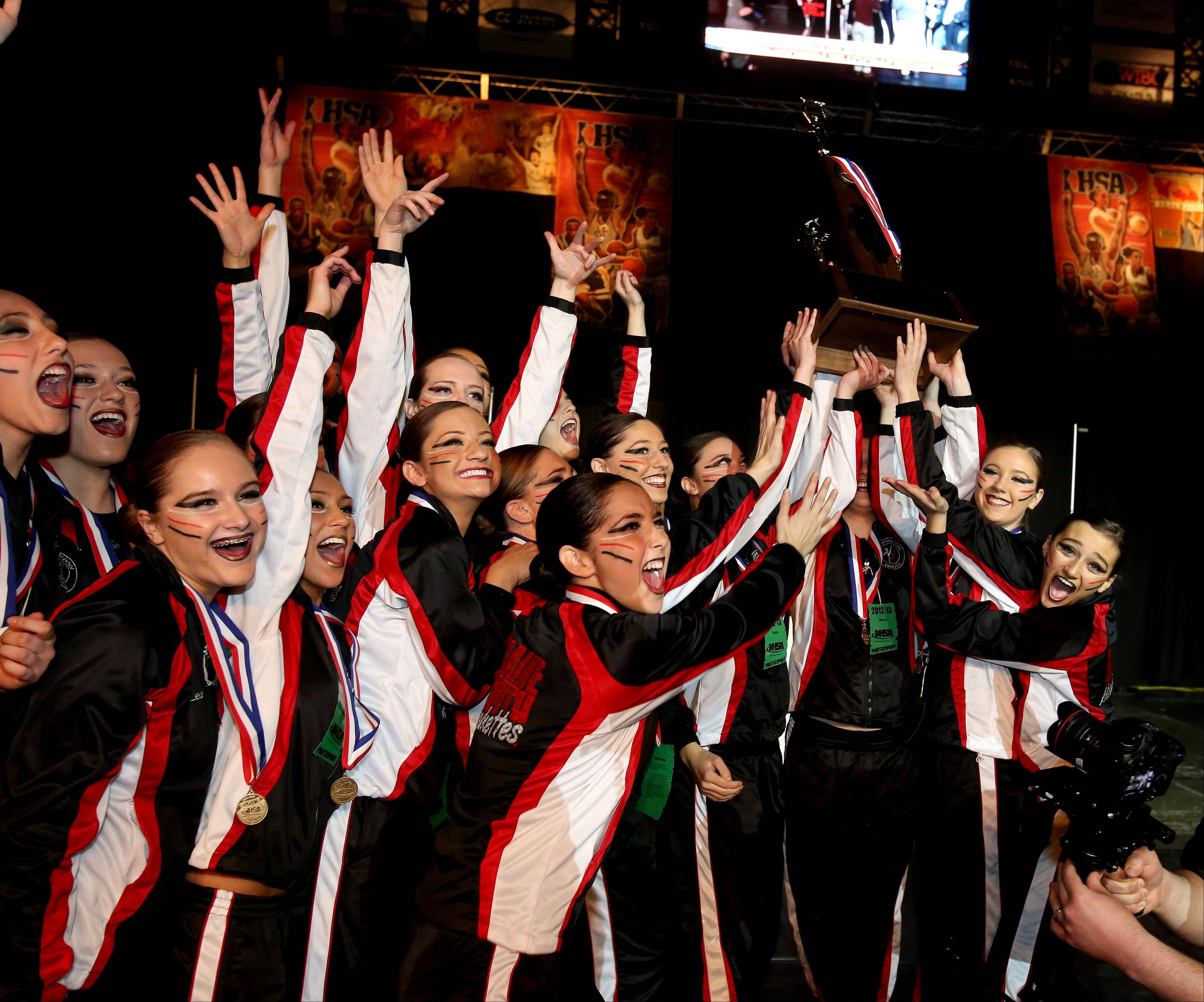 The Maine South High School dance team hold up their first place trophy in the 3A division at the Competitive Dance State Finals on Saturday in Bloomington.