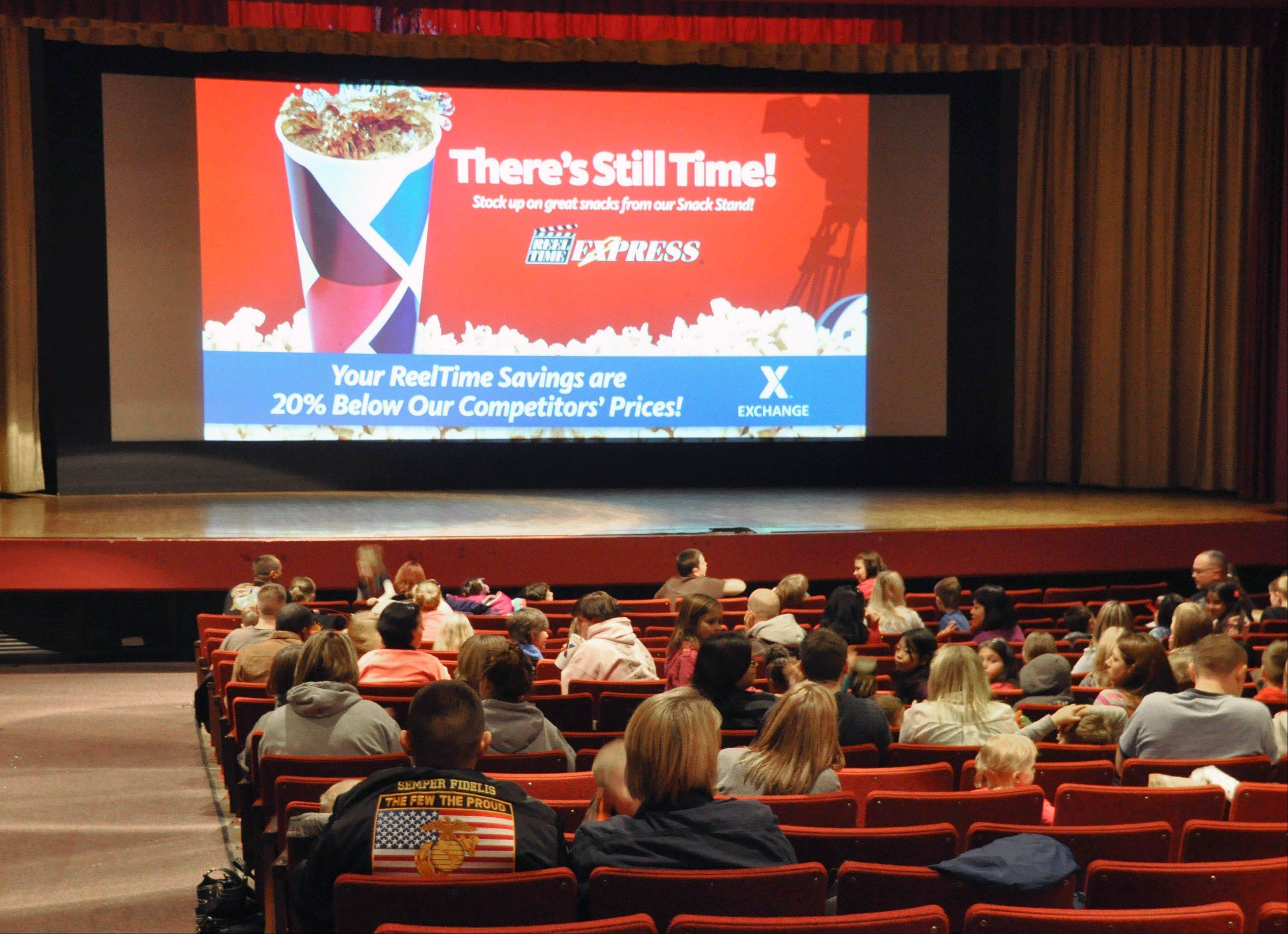 "Movie patrons wait for the showing of ""Hotel Transylvania"" inside the theater on Ellsworth Air Force Base in South Dakota on its last day of operation, Saturday, Jan. 19, 2013. The Army and Air Force Exchange Service theater serving airmen and their families is one of 60 across the globe that's closing because it's too expensive to switch from 35 millimeter film prints to an all-digital projection format."