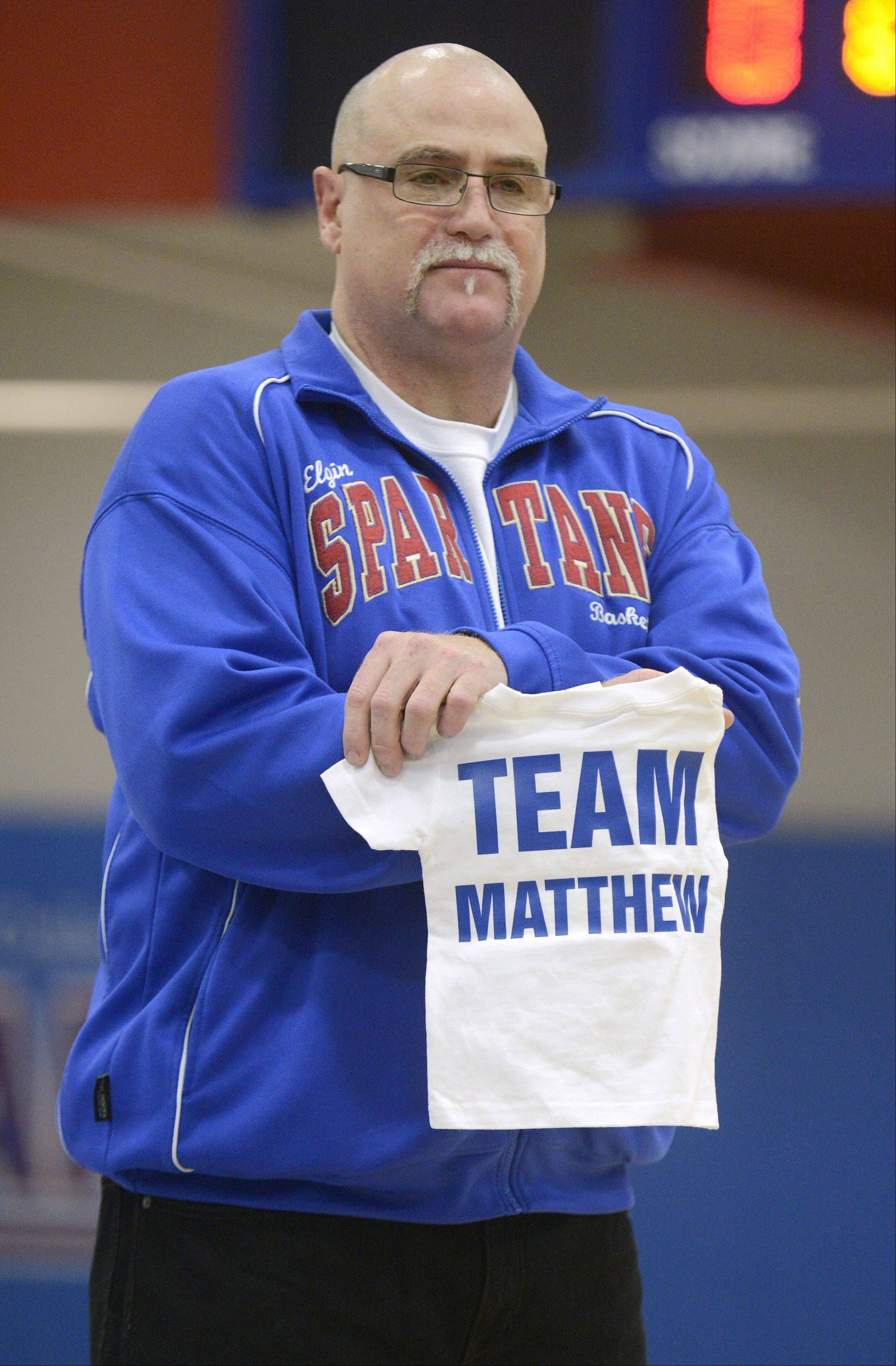 "Laura Stoecker/lstoecker@dailyherald.comElgin Community College Spartans assistant coach, Scott Cork, holds back tears as he shows the t-shirt made especially for Matthew Erickson, 1, of Huntley to welcome him to the mens basketball team during his ceremonial ""adoption"" on Saturday, January 26. Matthew, the son of South Elgin assistant baseball coach Ben Erickson, is fighting brain cancer."