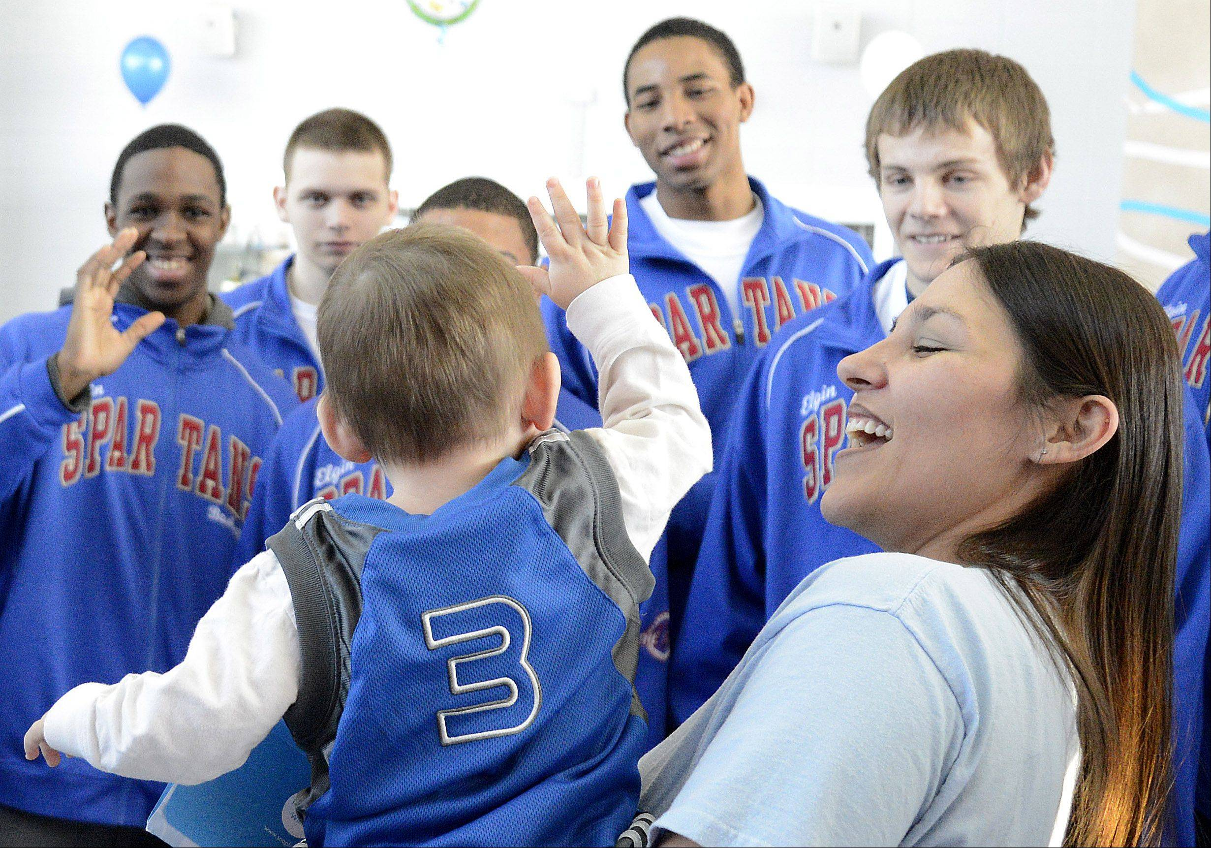 "Laura Stoecker/lstoecker@dailyherald.comSue Erickson of Huntley introduces her son, Matthew, 1, to the mens basketball team of Elgin Community College before his ""adoption"" ceremony by the team on Saturday, January 26. Matthew is the son of South Elgin assistant baseball coach Ben Erickson, and is fighting brain cancer. The team was able to ""adopt"" Matthew through the Friends of Jaclyn"" program."