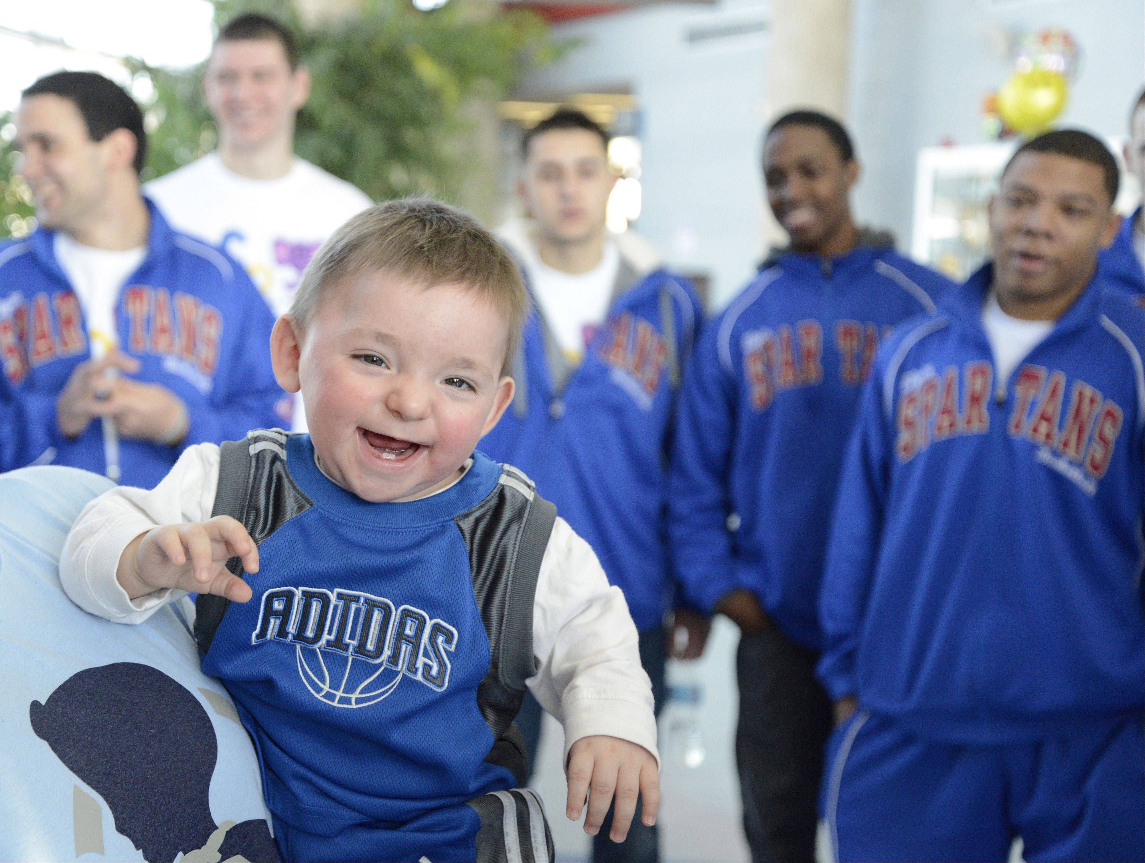 "Laura Stoecker/lstoecker@dailyherald.comMatthew Erickson, 1, of Huntley is introduced to members of the Spartans mens basketball team at Elgin Community College before his ""adoption"" ceremony on Saturday, January 26. Matthew, the son of South Elgin assistant baseball coach Ben Erickson, is fighting brain cancer. The team was able to ""adopt"" Matthew through the Friends of Jaclyn"" program."