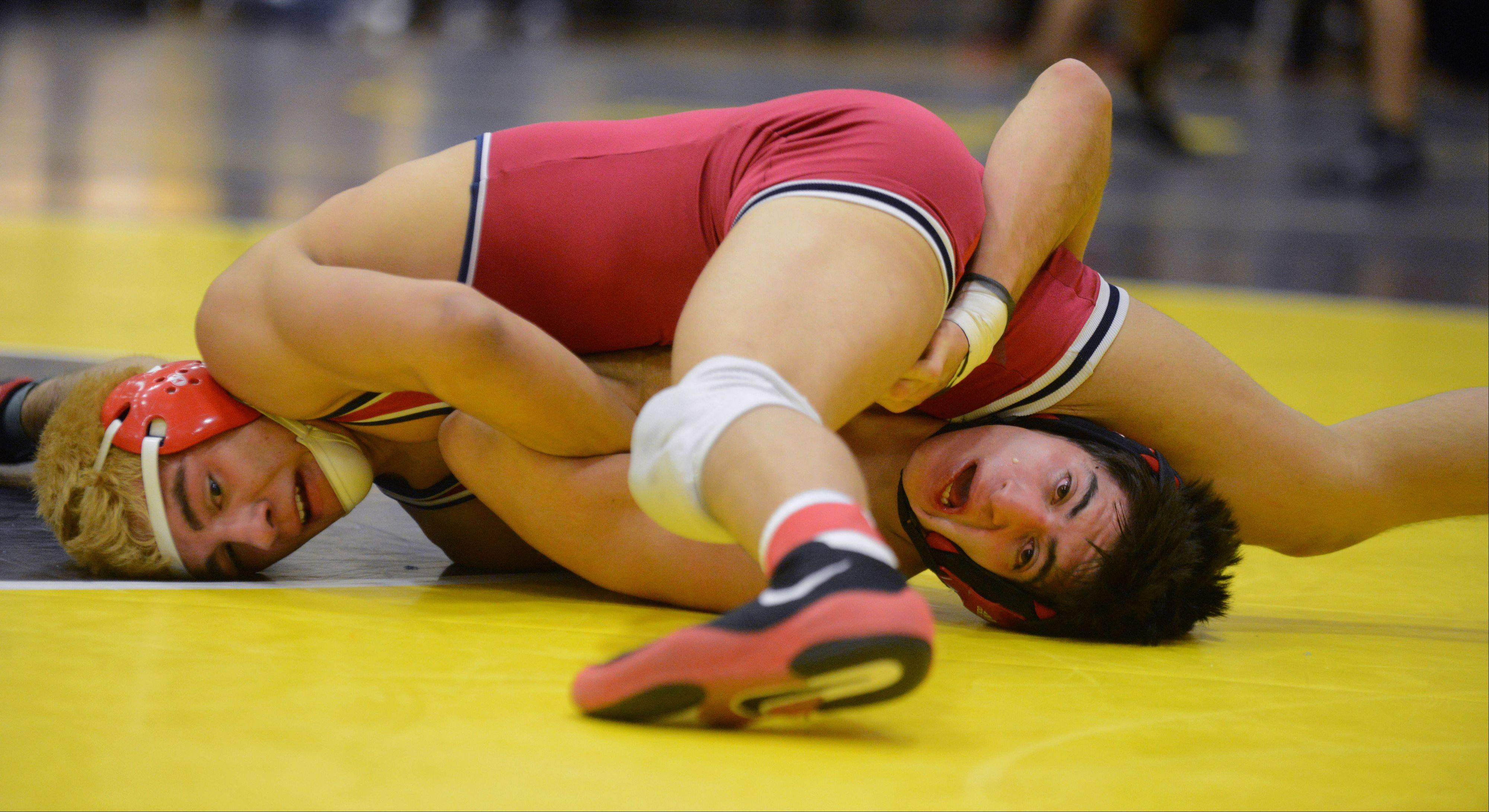 Brandon Farias of West Aurora,left, and Gustavo Garcia take part in a 152 pound match during the DuPage Valley Conference wrestling meet in Carol Stream Saturday.