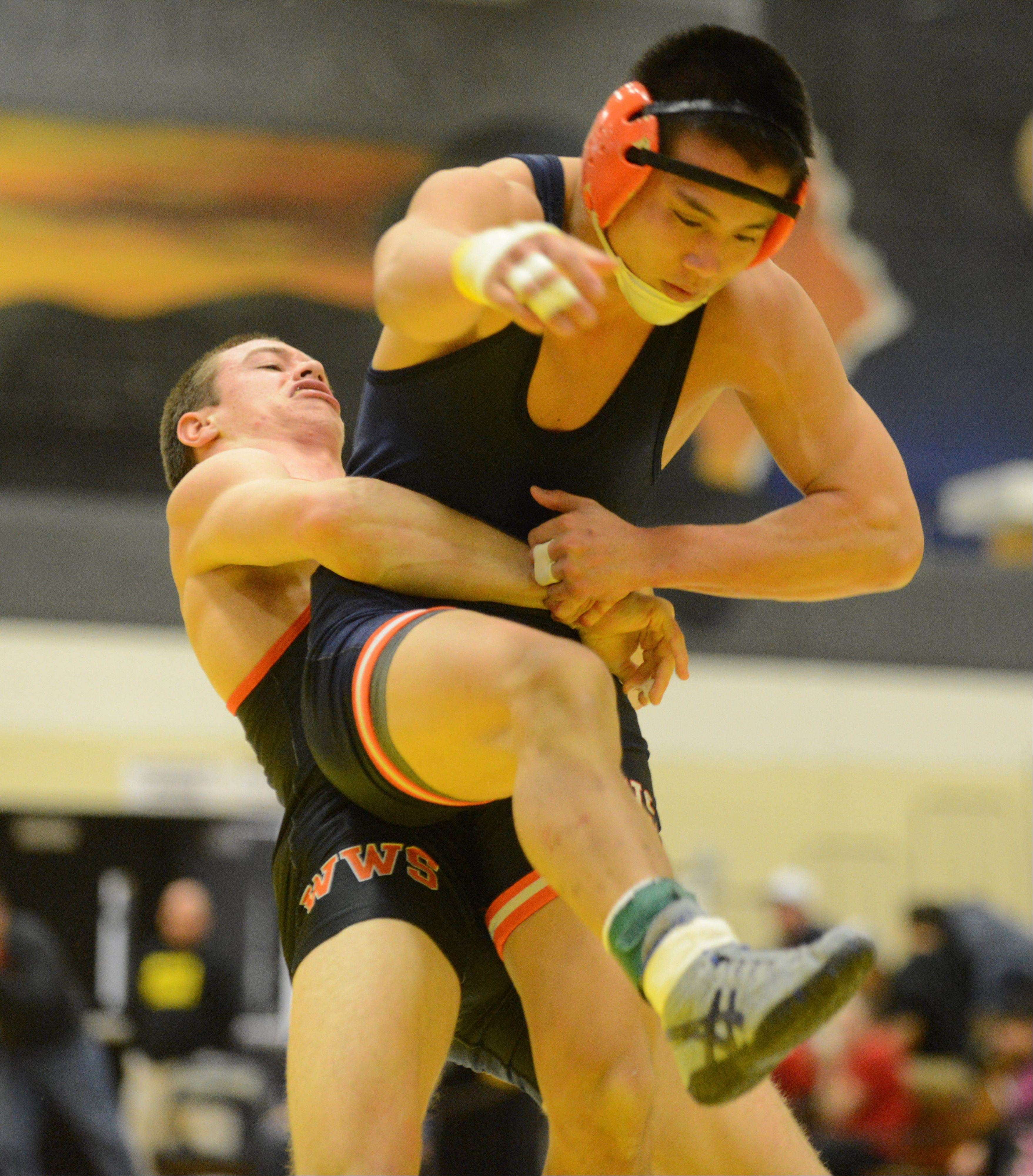 Andrew Ives of Wheaton Warrenville South,left, lifts lifts Chris Junior of Naperville north during a 152 pound match at the DuPage Valley Conference wrestling meet in Carol Stream Saturday.