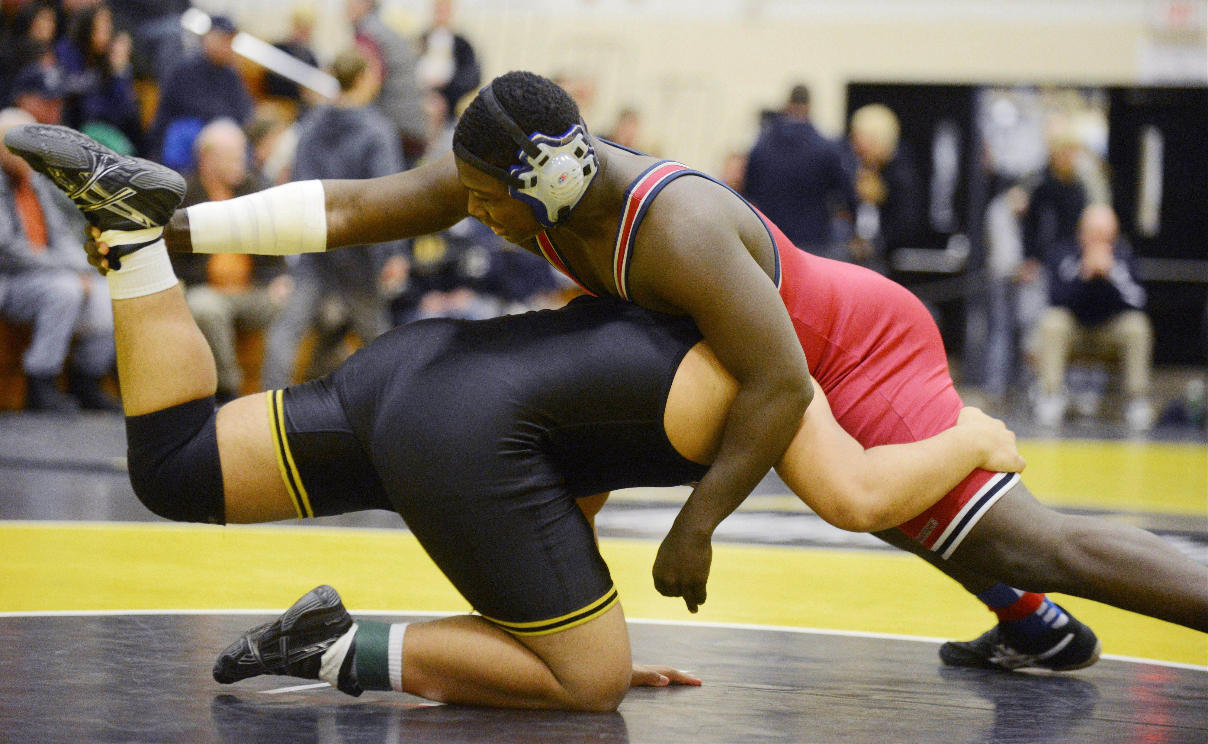 Paul Pennington of Glenbard North and Marquetas Ward take part in a 220 pound match during the DuPage Valley Conference wrestling meet Saturday in Carol Stream.